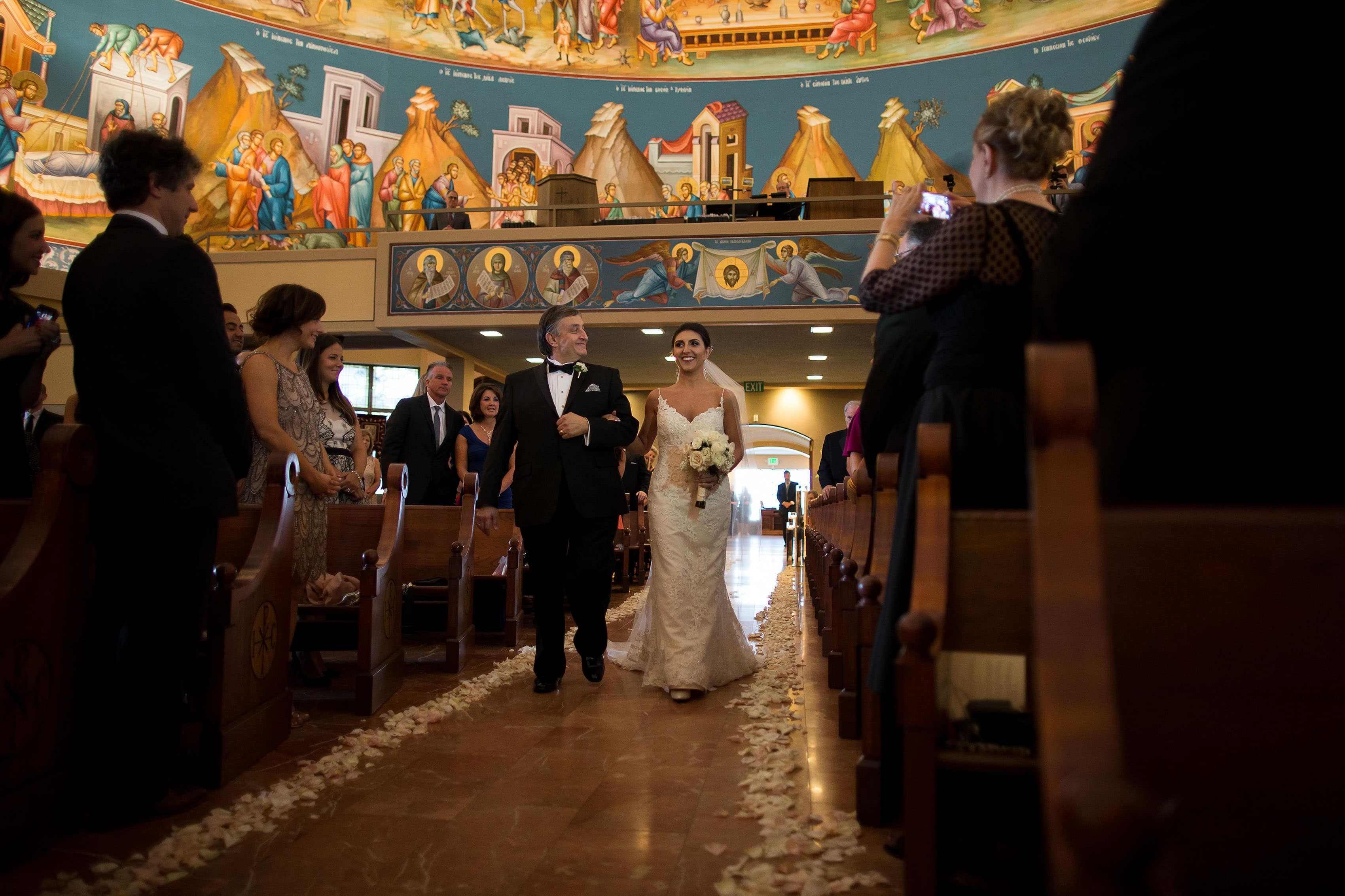 Marika walks down the aisle with her father at Assumption Greek Orthodox Cathedral