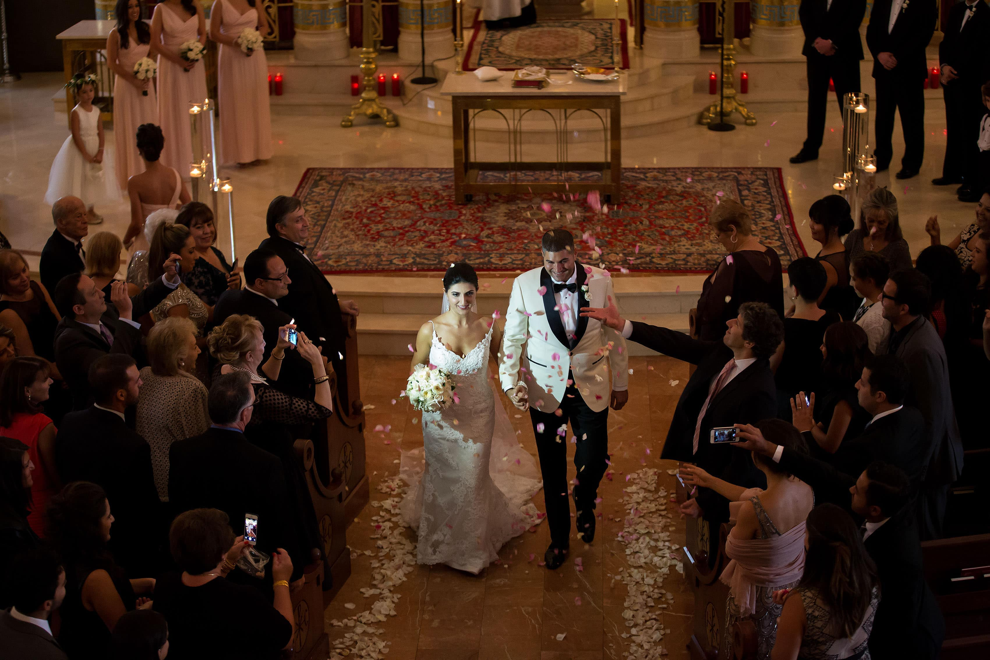 The couple are showered with rose pedals during their Denver Greek wedding at Assumption Greek Orthodox Cathedral