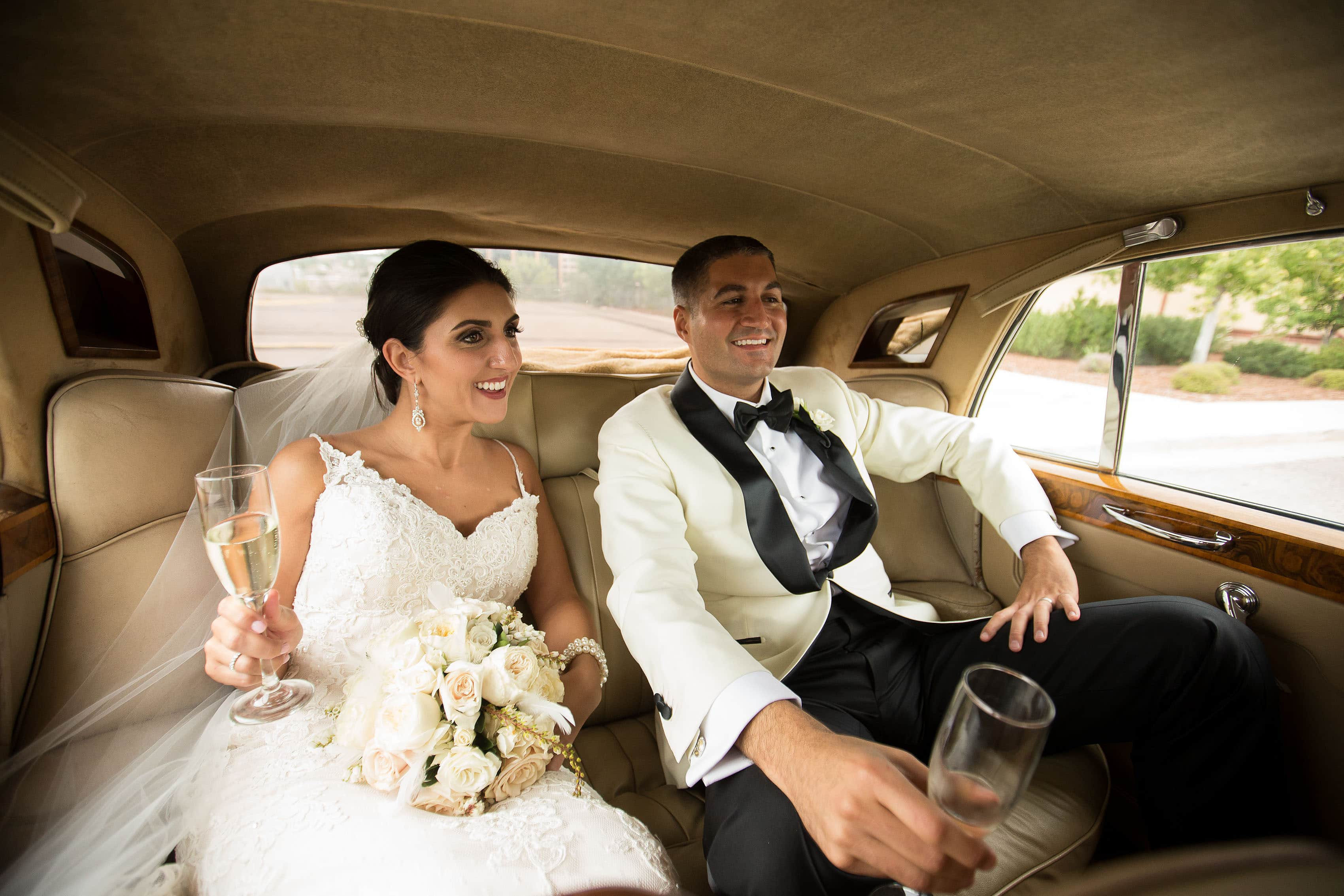 Marika and Dean ride together in a Rolls Royce during their Denver Greek Grand Hyatt wedding