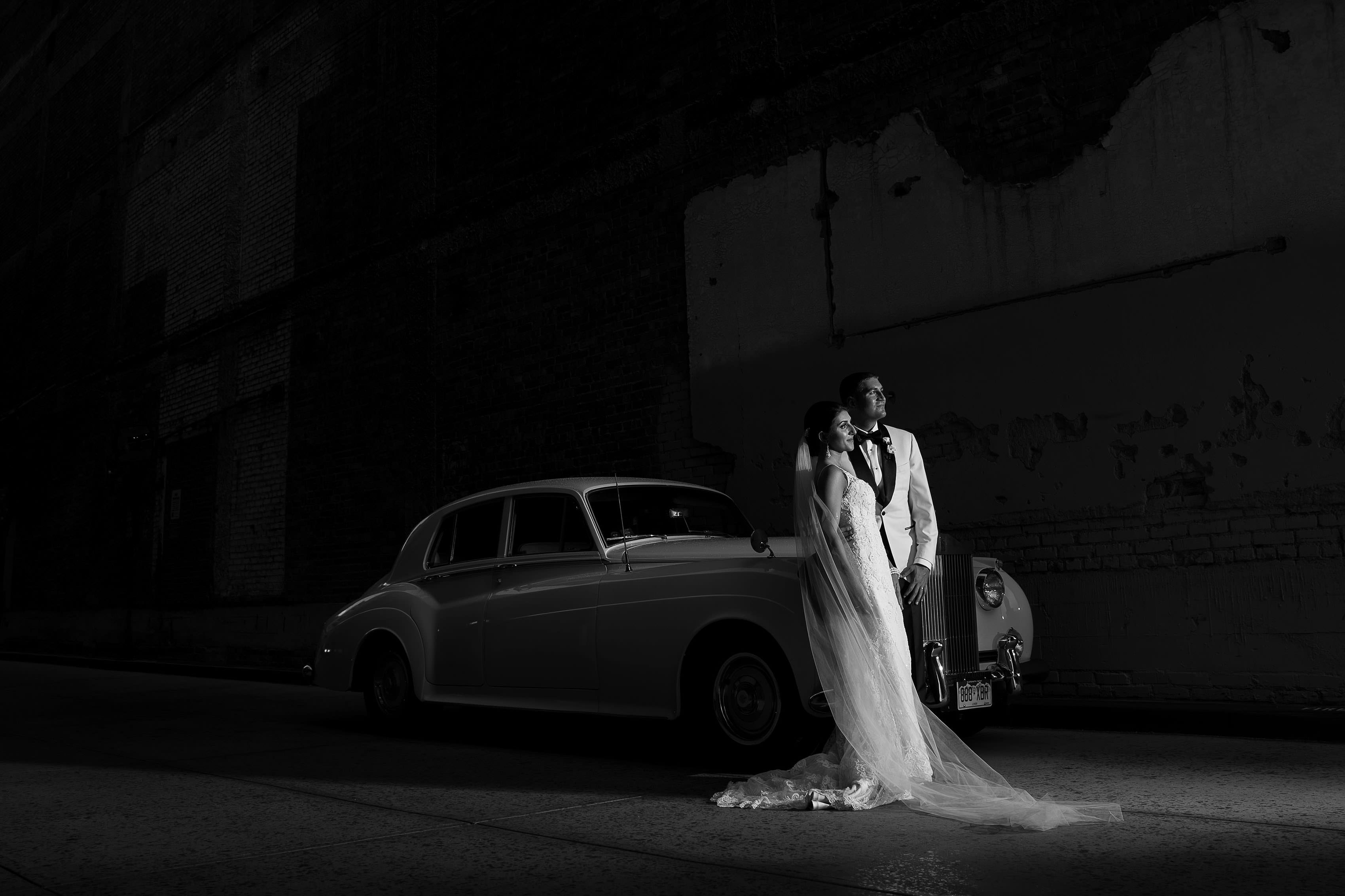 The couple pose with a Rolls Royce during their Denver Greek Grand Hyatt wedding