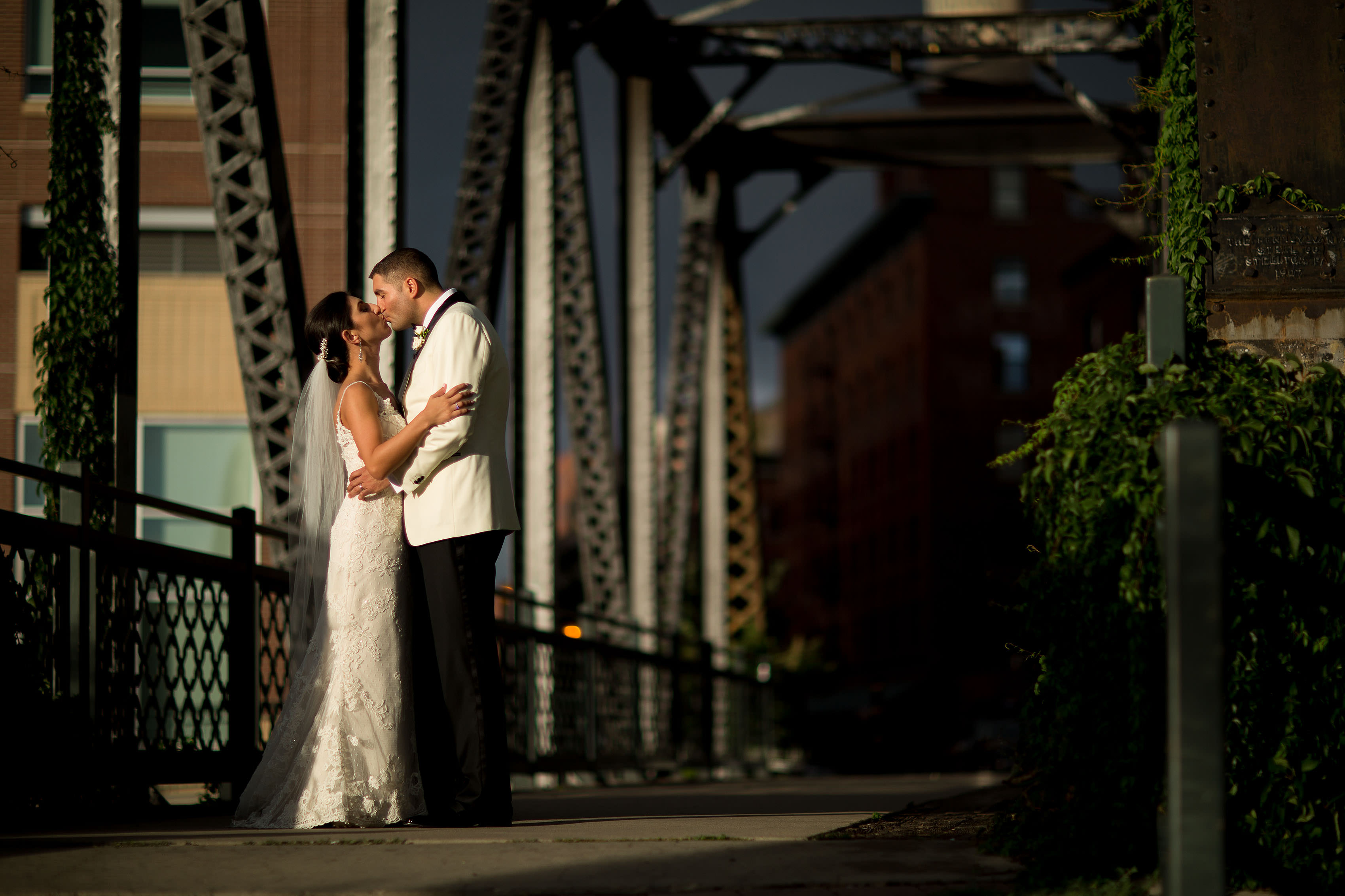 Marika and Dean share a kiss outside on the Wynkoop Street bridge during their Denver Greek Grand Hyatt wedding