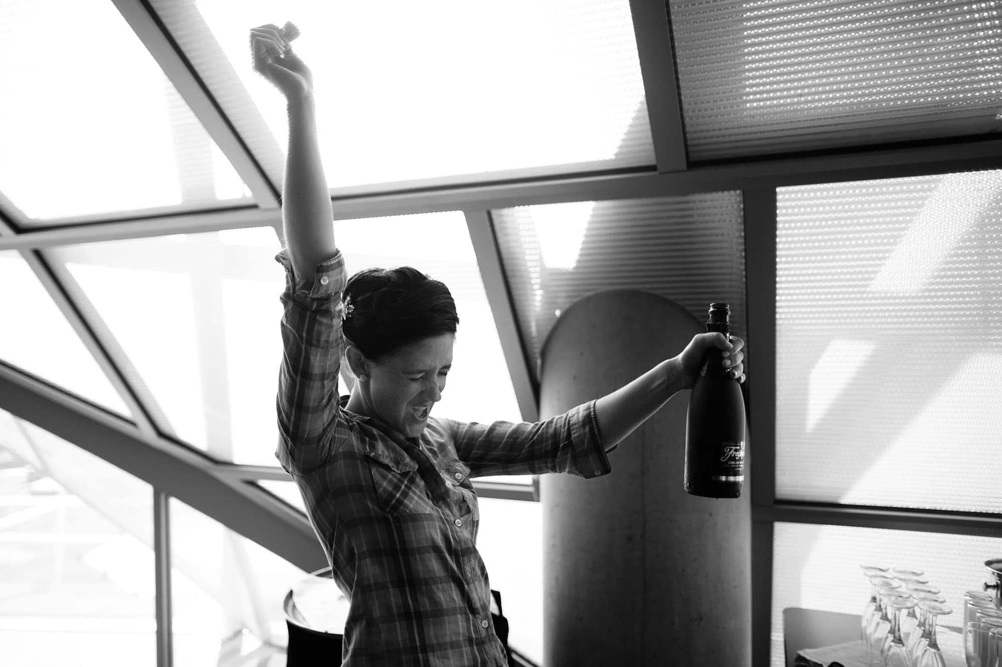 Amanda cracks open a bottle of champagne