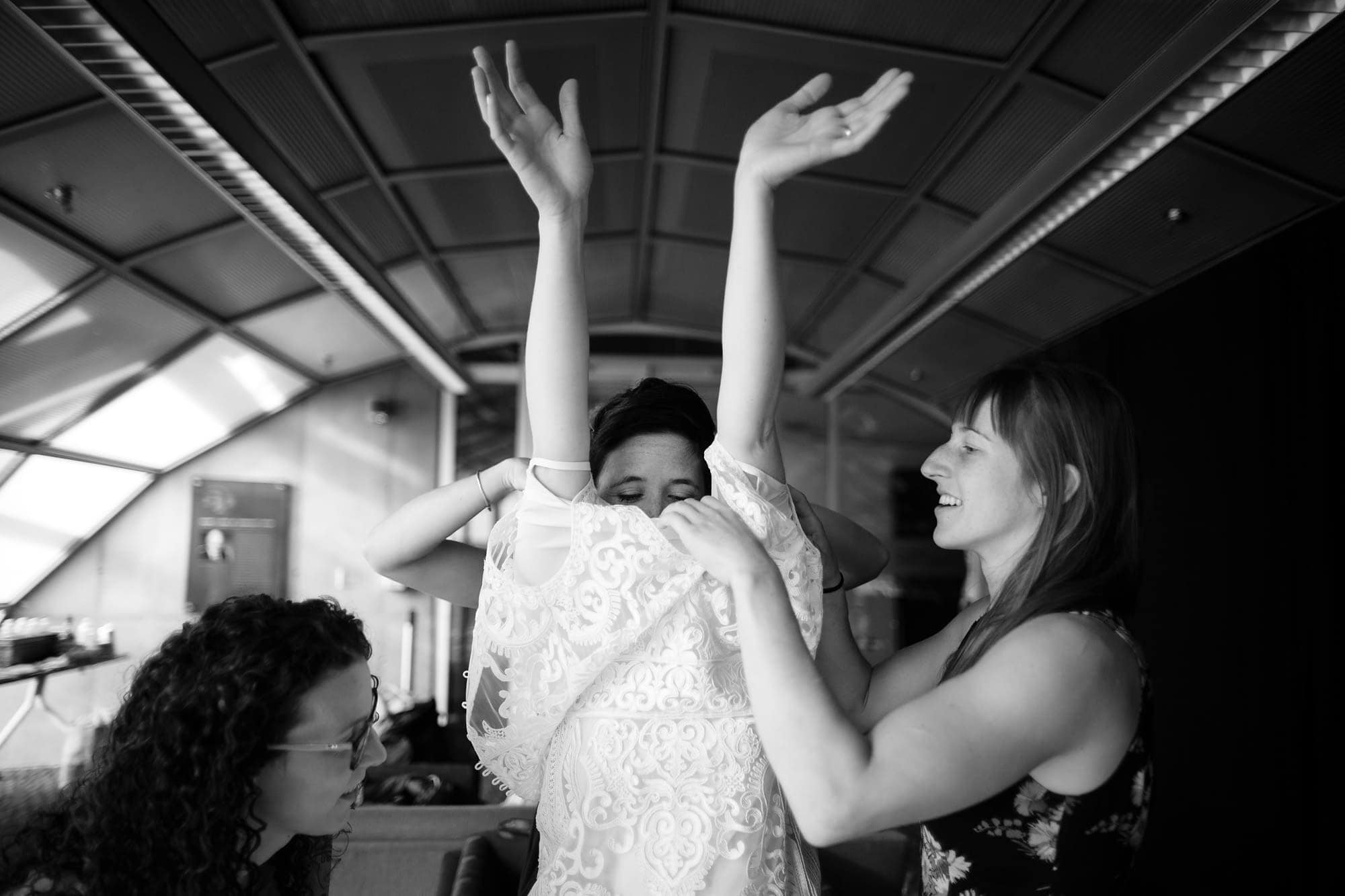 Amanda gets help putting on her dress in the bridal suite