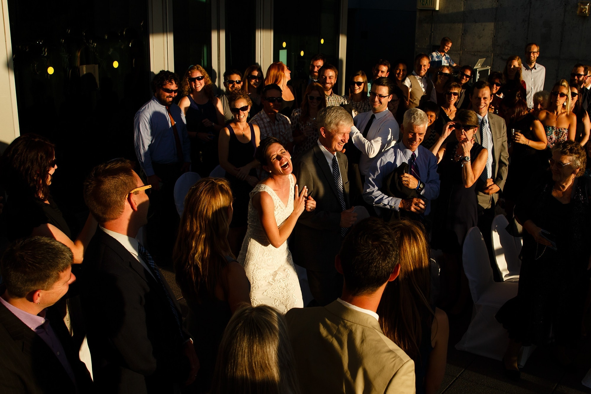 Bride Amanda laughs while walking down the aisle at the Denver Museum of Nature and Science