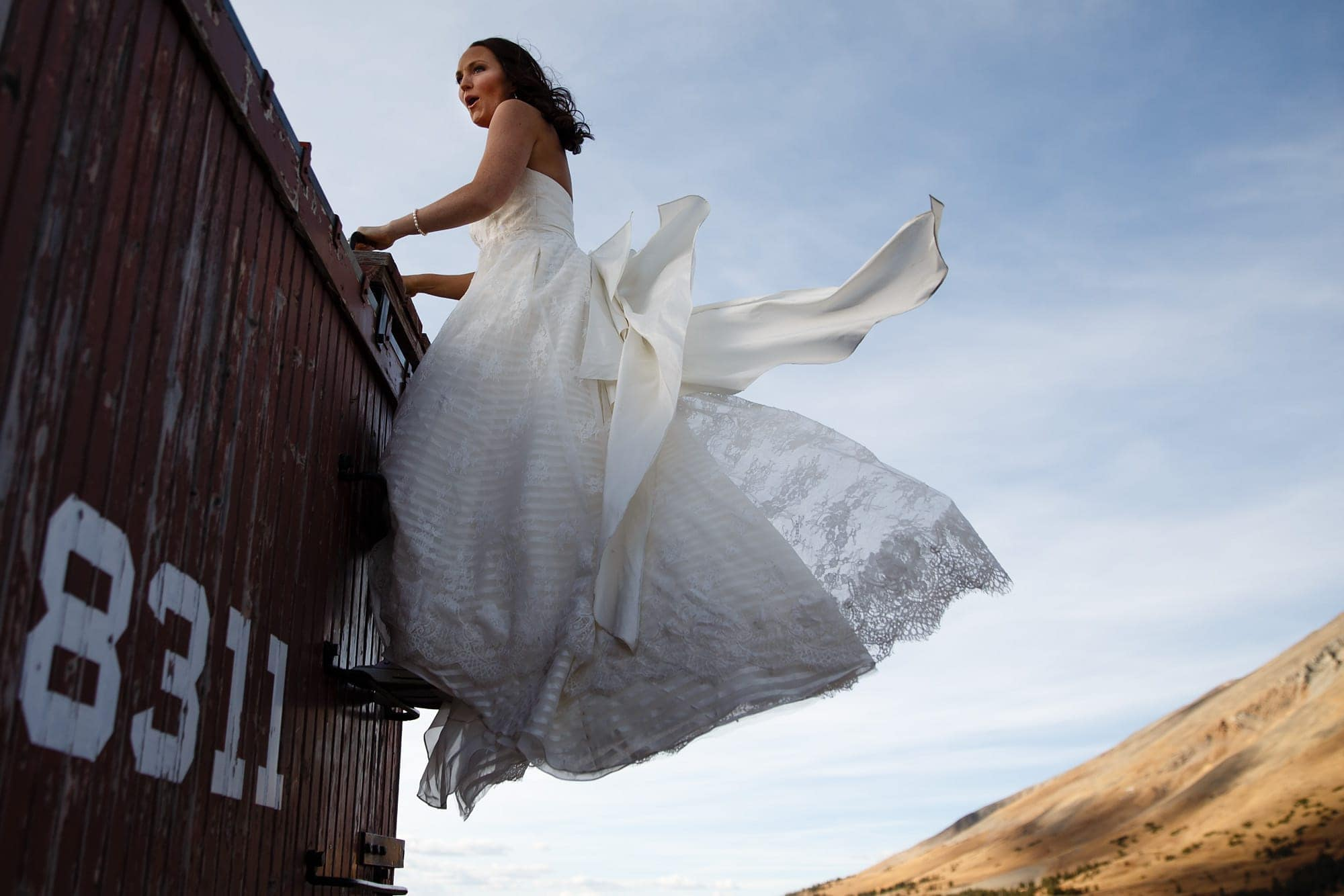 Bride Heidi climbs on a box car during her Breckenridge Boreas Pass wedding