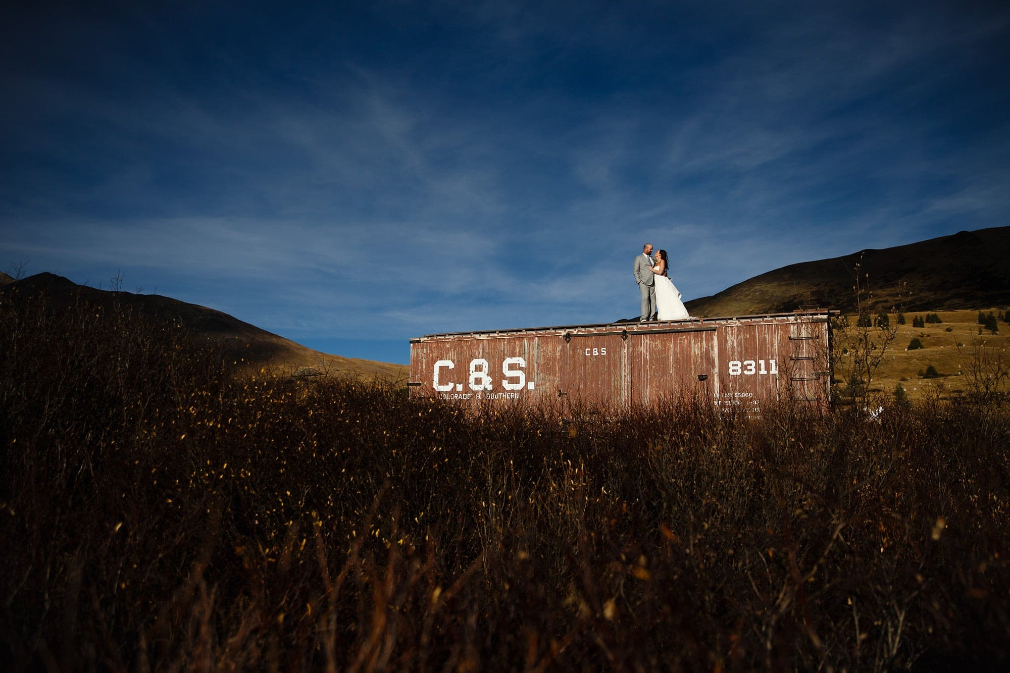 Heidi and Frank stand on a boxcar during their Breckenridge Boreas Pass wedding