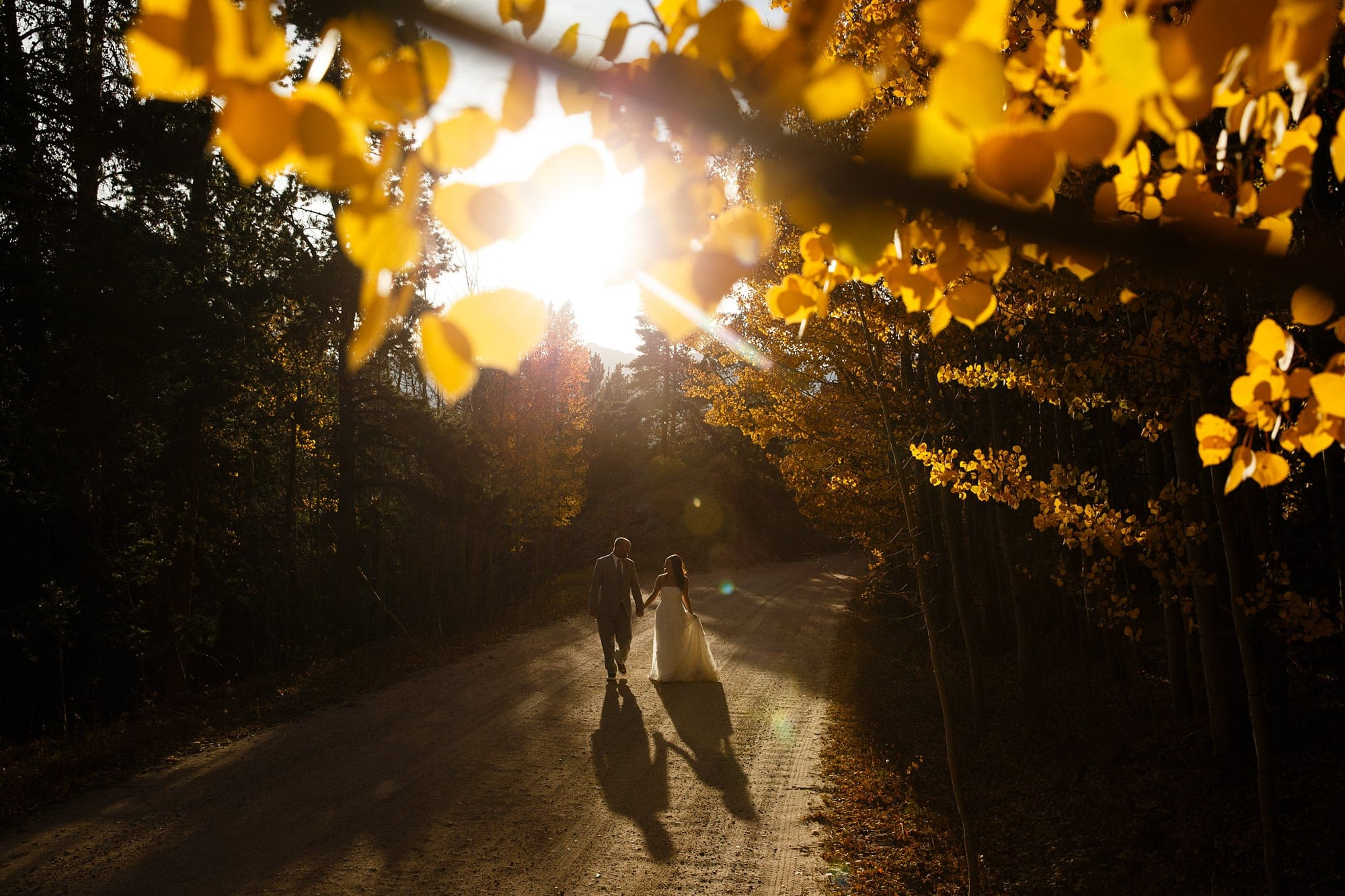 Frank and Heidi walk along a dirt road as the golden aspen trees are illuminated by the setting sun on Boreas Pass near Breckenridge during their wedding