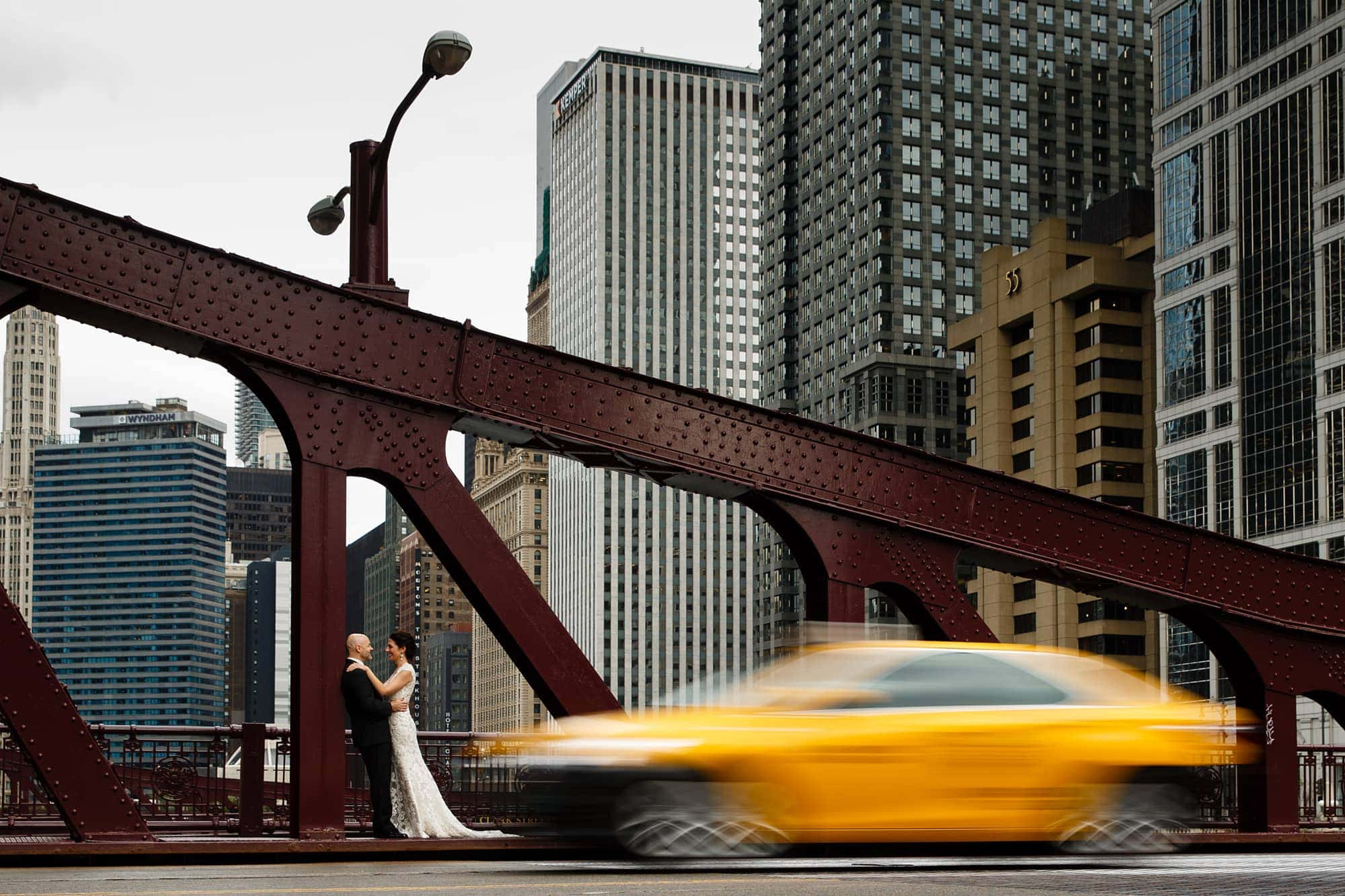 Christina and Brad share a moment together on their wedding day near the State Street bridge as a taxi drives by