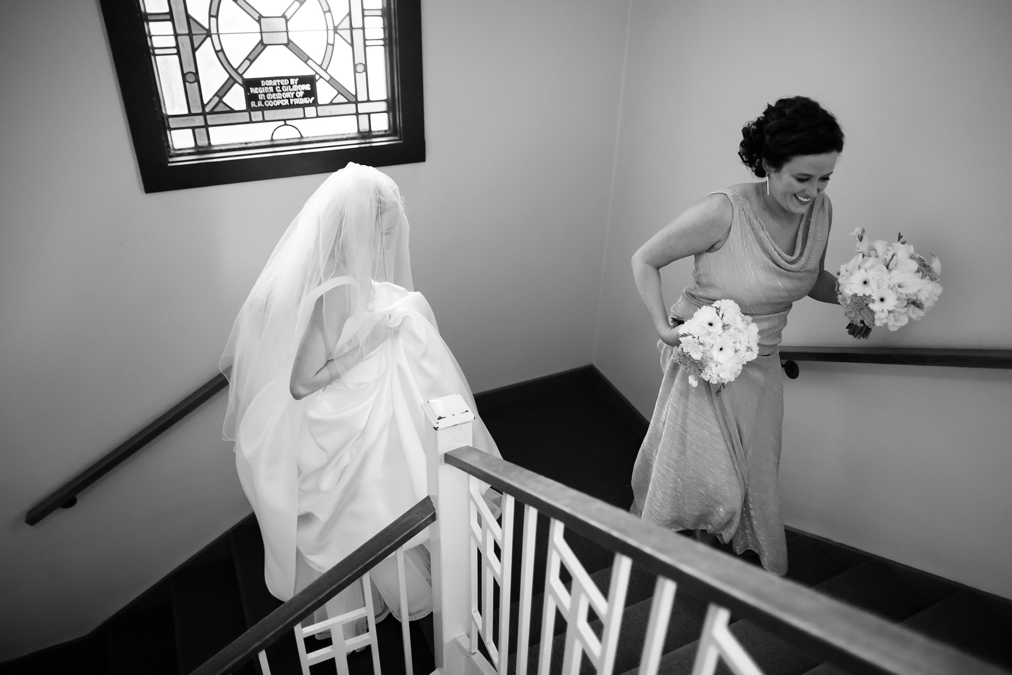 Bride Shannon walks up the stairs at Cathedral of Saint Raphael