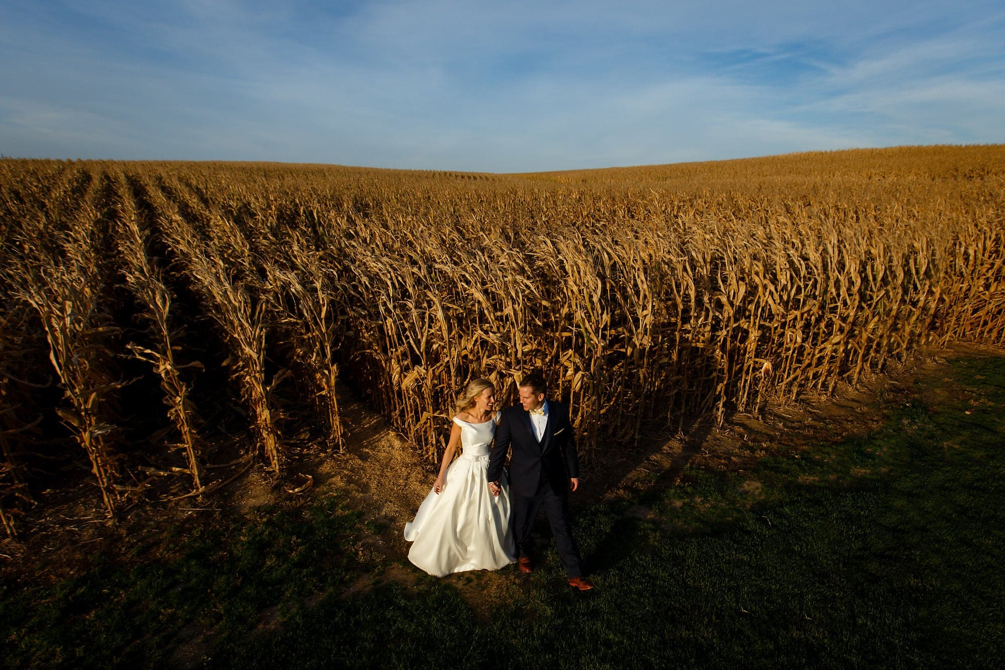 A bride and groom walk out of the cornfield during their Field of Dreams wedding