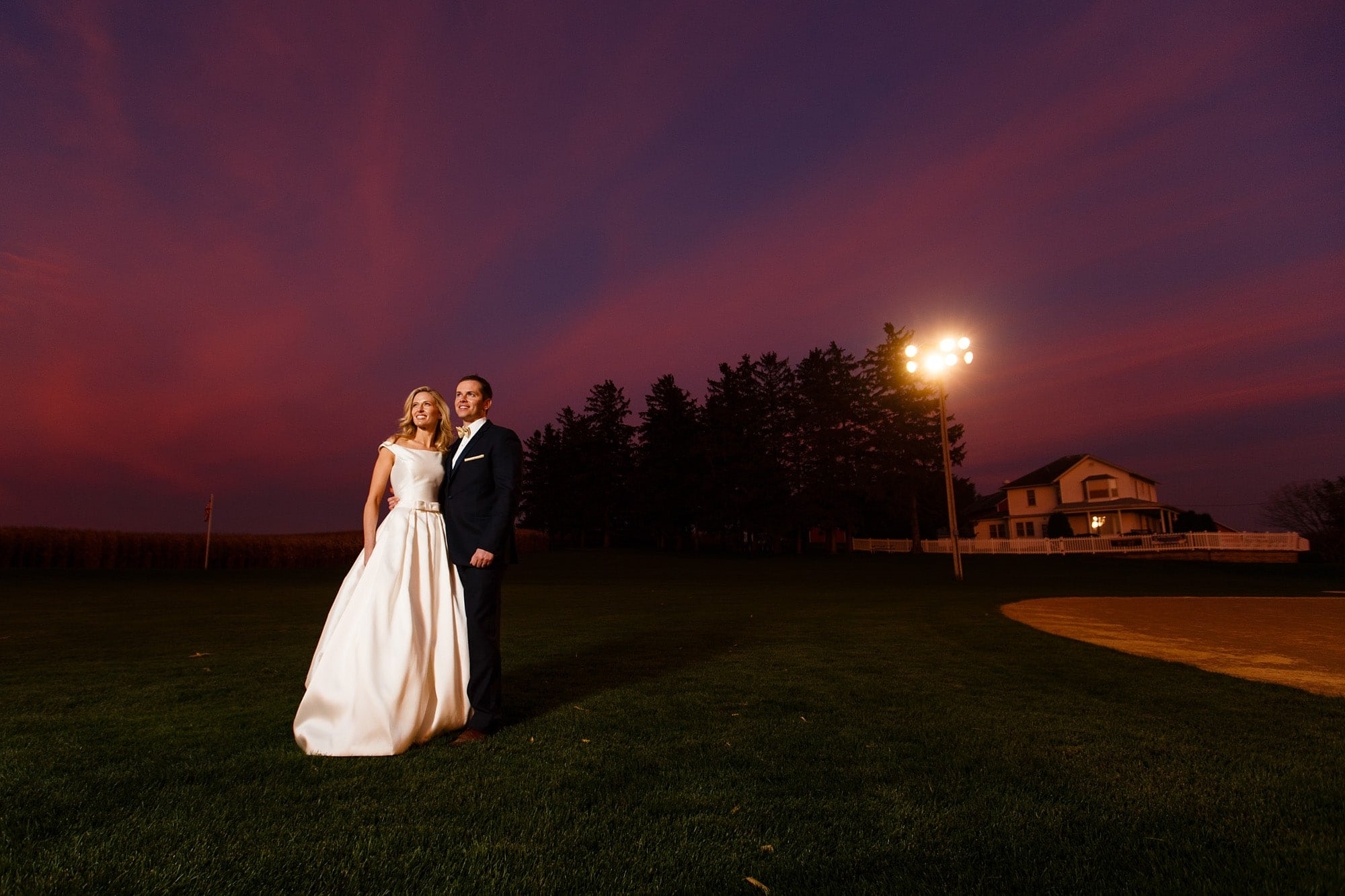 The sun sets as Shannon and David pose at the during their Field of Dreams wedding in Dyersville, Iowa