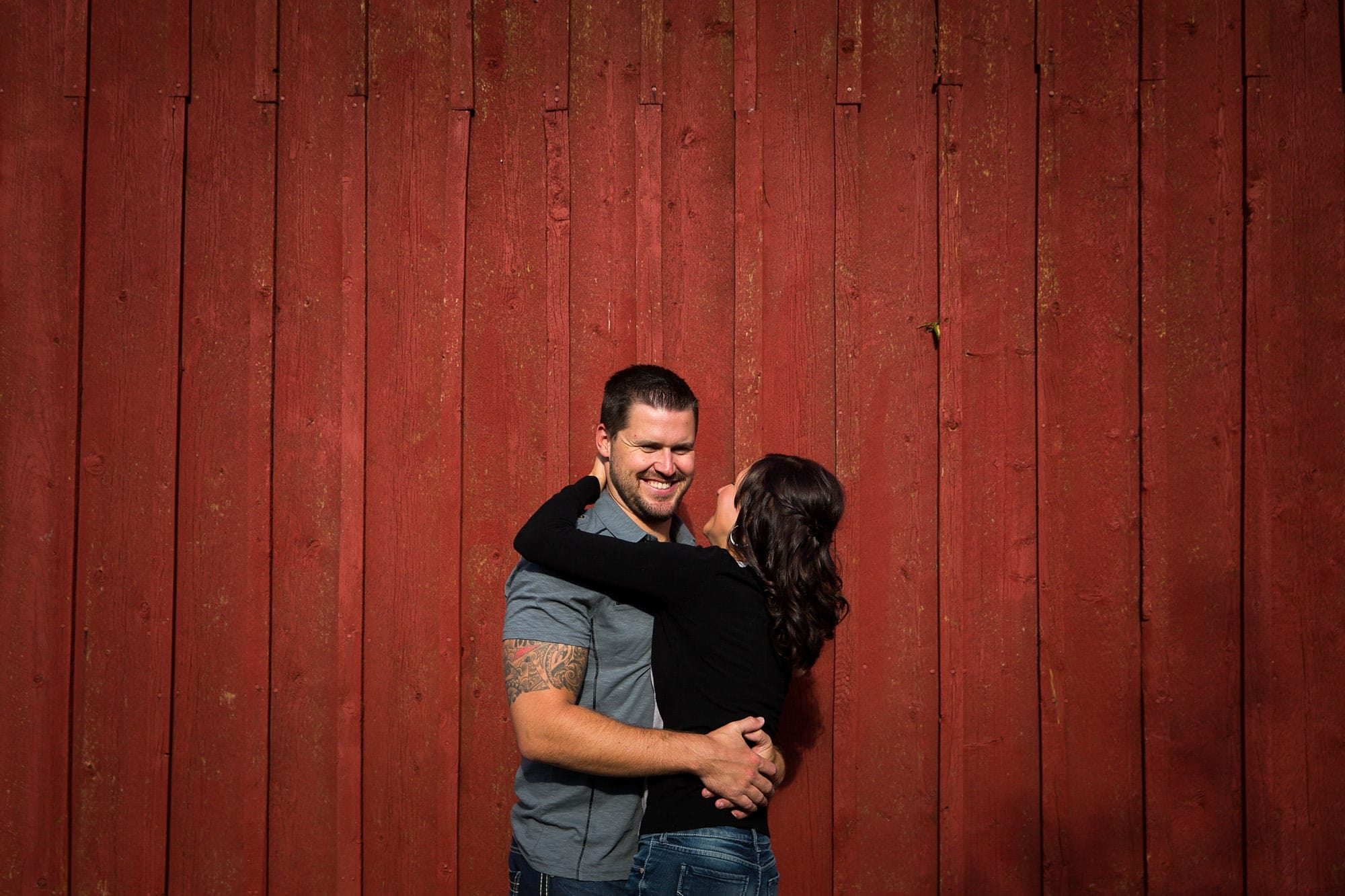 Nick laughs with Melanie against a red barn wall during their Golden, Colorado engagement session