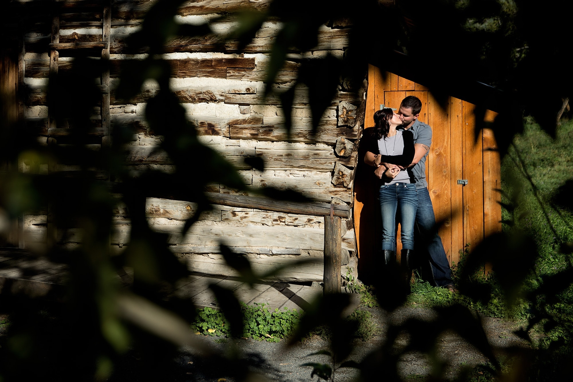 Nick kisses Melanie against a barn wall during their Golden, Colorado engagement session