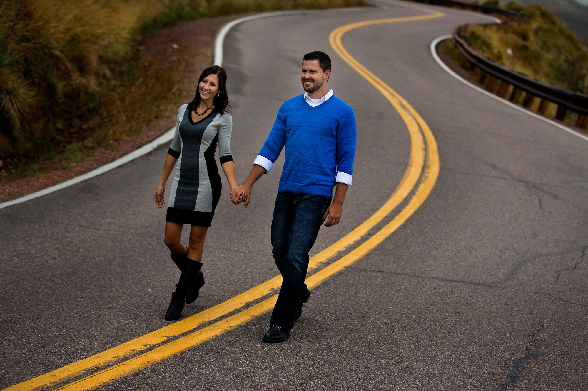 Nick and Melanie walk on the road during their Lookout mountain engagement photos session in Golden, Colorado.
