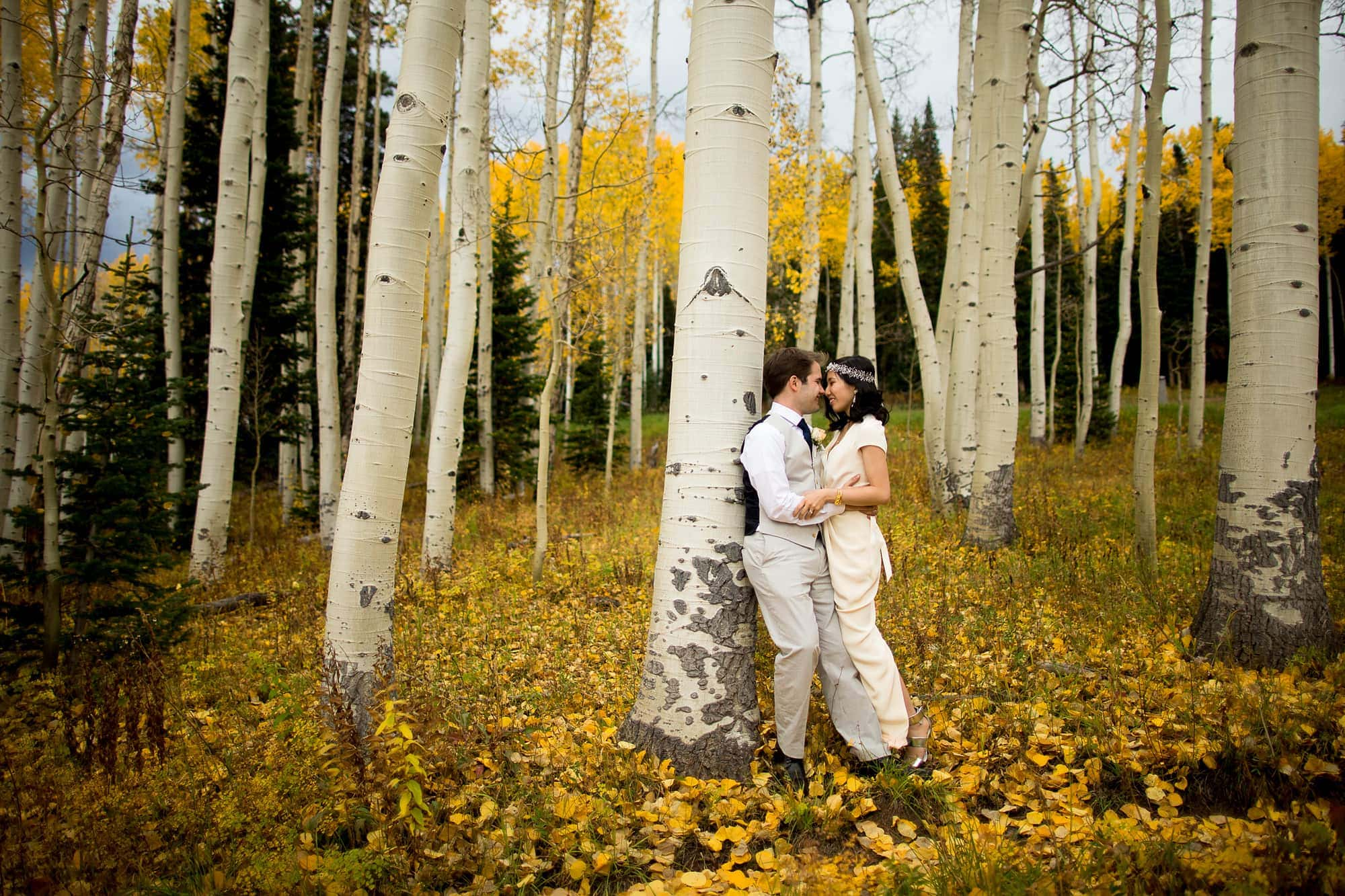 Allison and Walker share a moment together amongst the aspen trees after their Lynn Britt Cabin wedding in Snowmass Village near Aspen, Colorado.