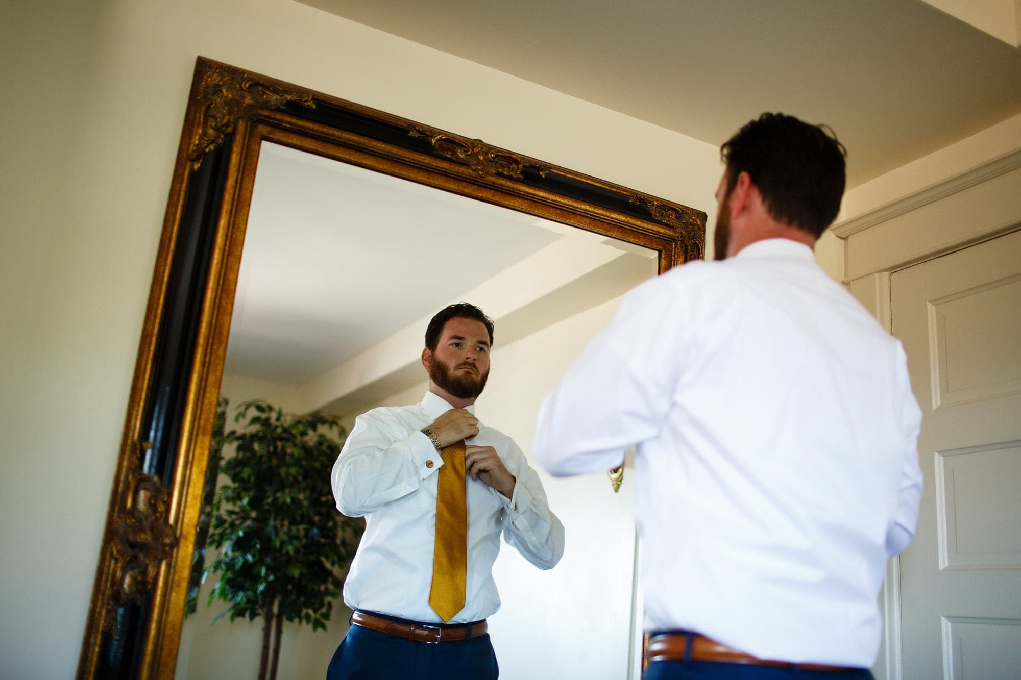 Blake Cannon ties his tie before his Willow Ridge Manor wedding