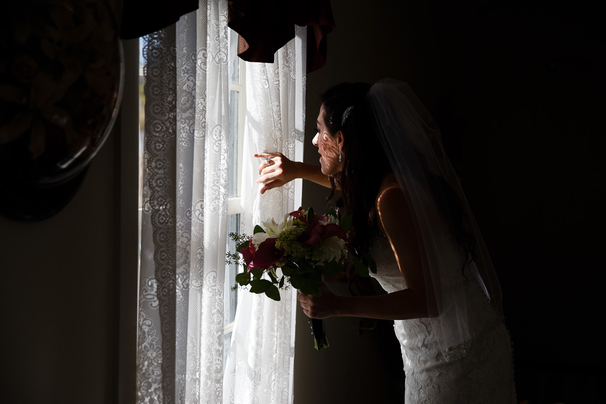 Bride Gina looks out the window before her Willow Ridge Manor wedding