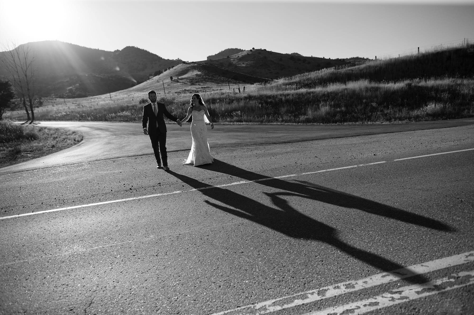 Blake leads Gina across the road during their wedding photos near The Fort restaurant in Morrison, Colorado after getting married at Willow Ridge Manor