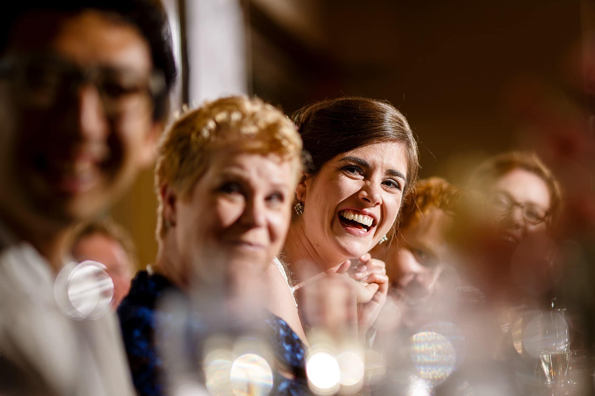 A bride laughs while her brother goves a toast during the reception at Rembrandt Yard in Boulder