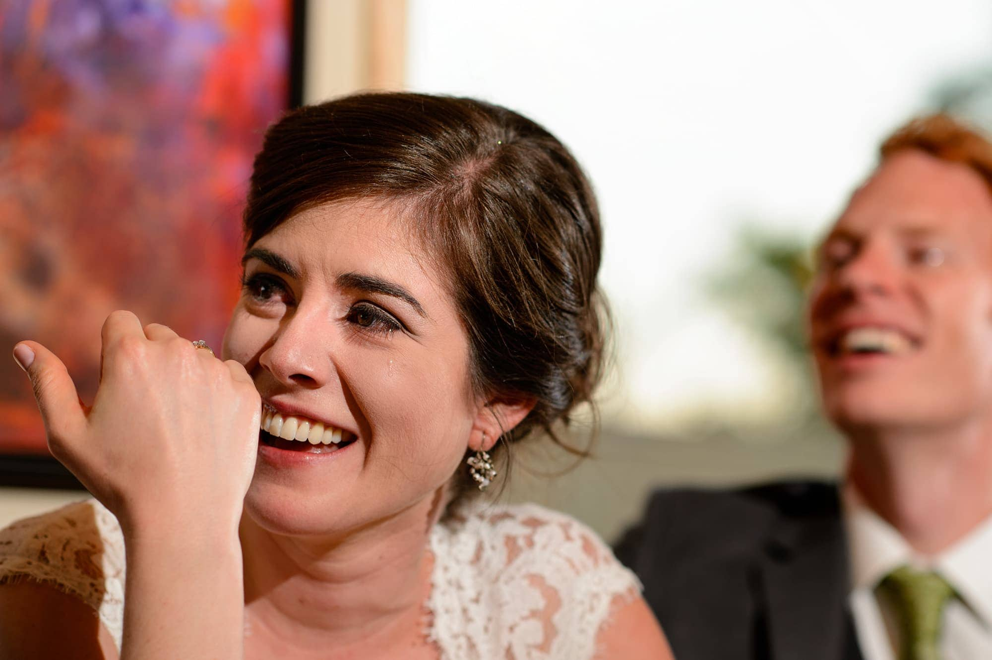 A bride cries and tears fall on her cheek during a toast from her brother at Rembrandt Yard
