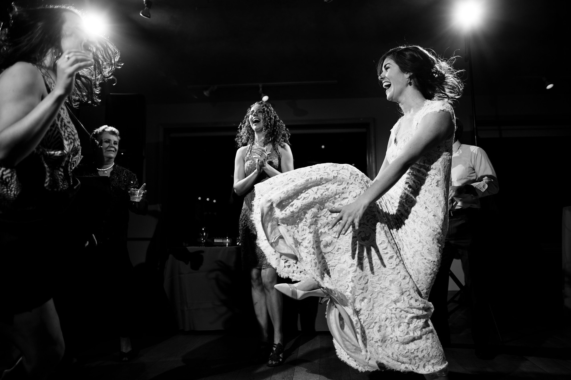 The bride boogies on the dance floor with friends during her wedding at Rembrandt Yard in Boulder