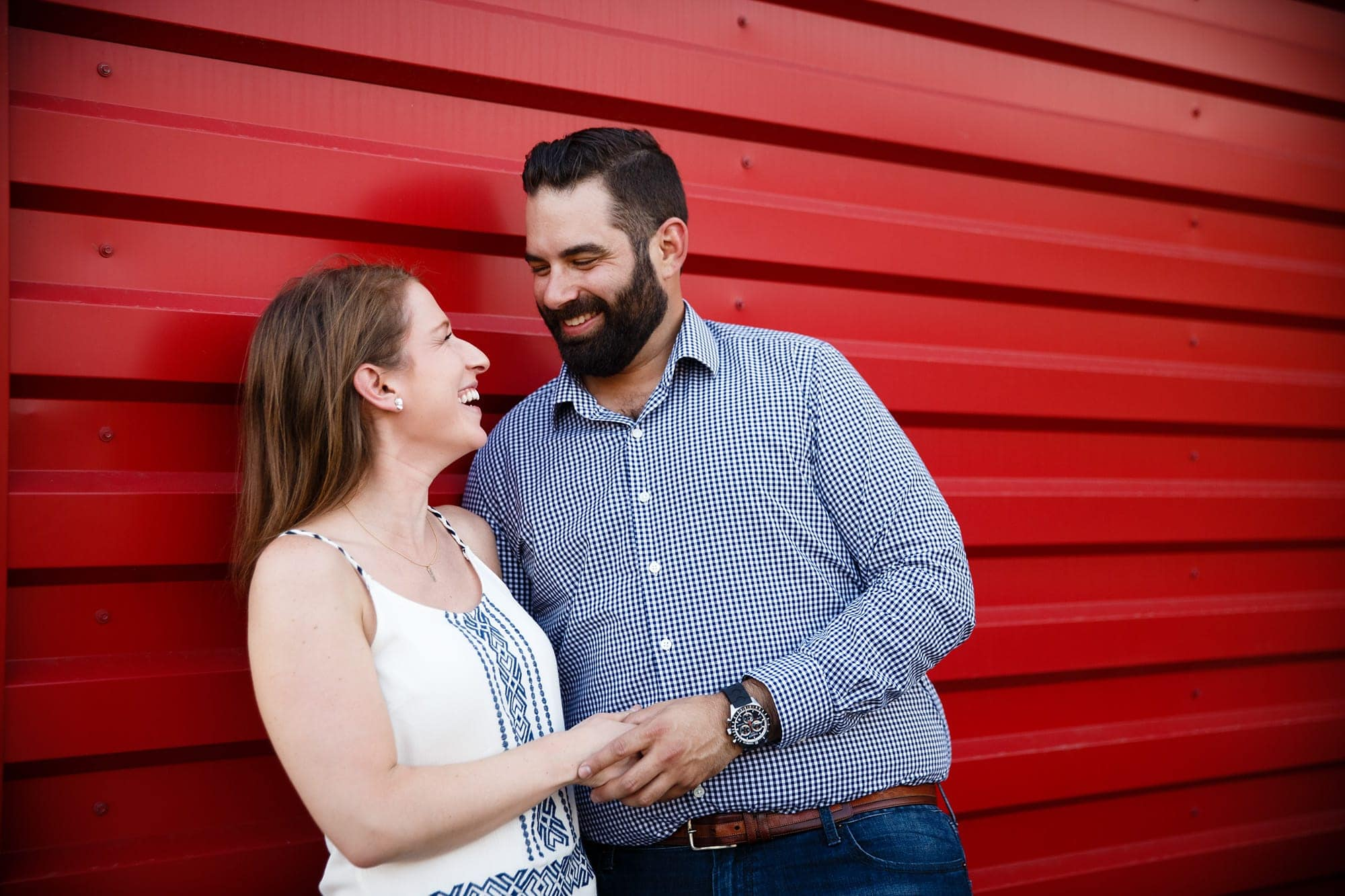 Devan and Josh share a laugh near Avanti in the LoHi neighborhood during their engagement session