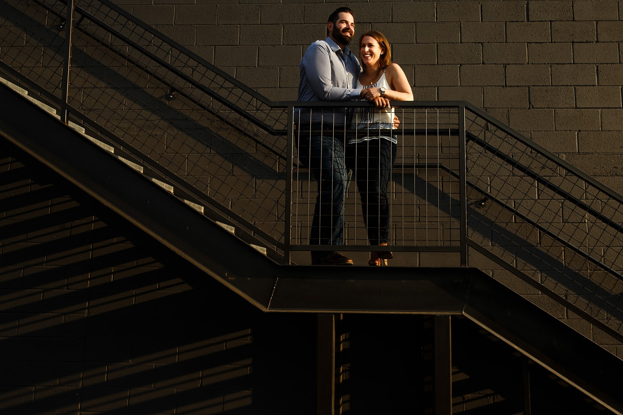 Devan and Josh embrace on a staircase near Avanti in the Lower Highlands during their engagement session