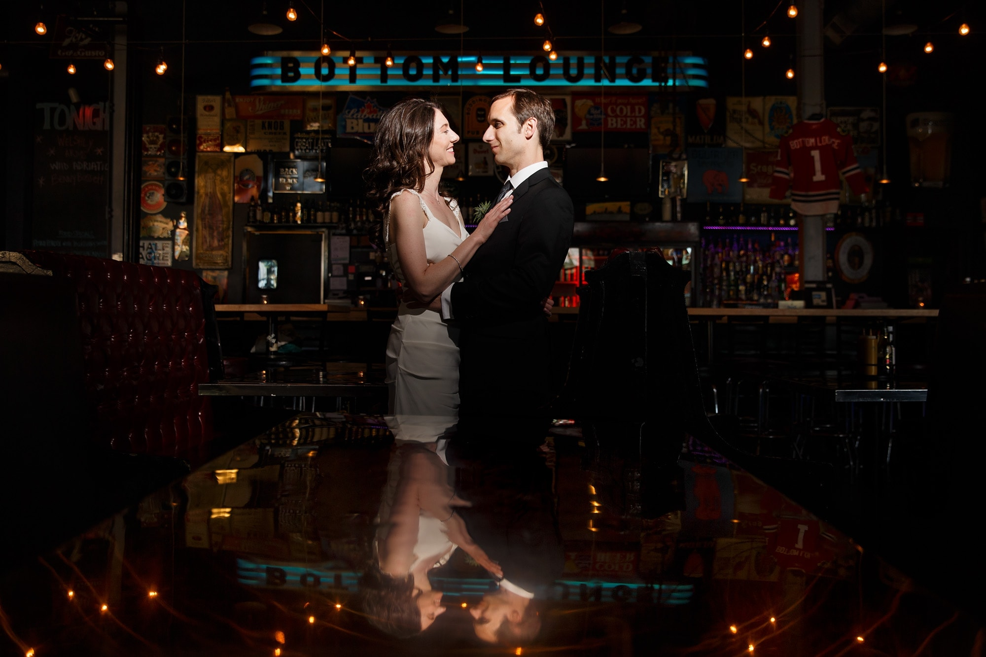 A couple staring into each others eyes are reflected into a table inside Bottom Lounge after their wedding in Chicago, Illinois.