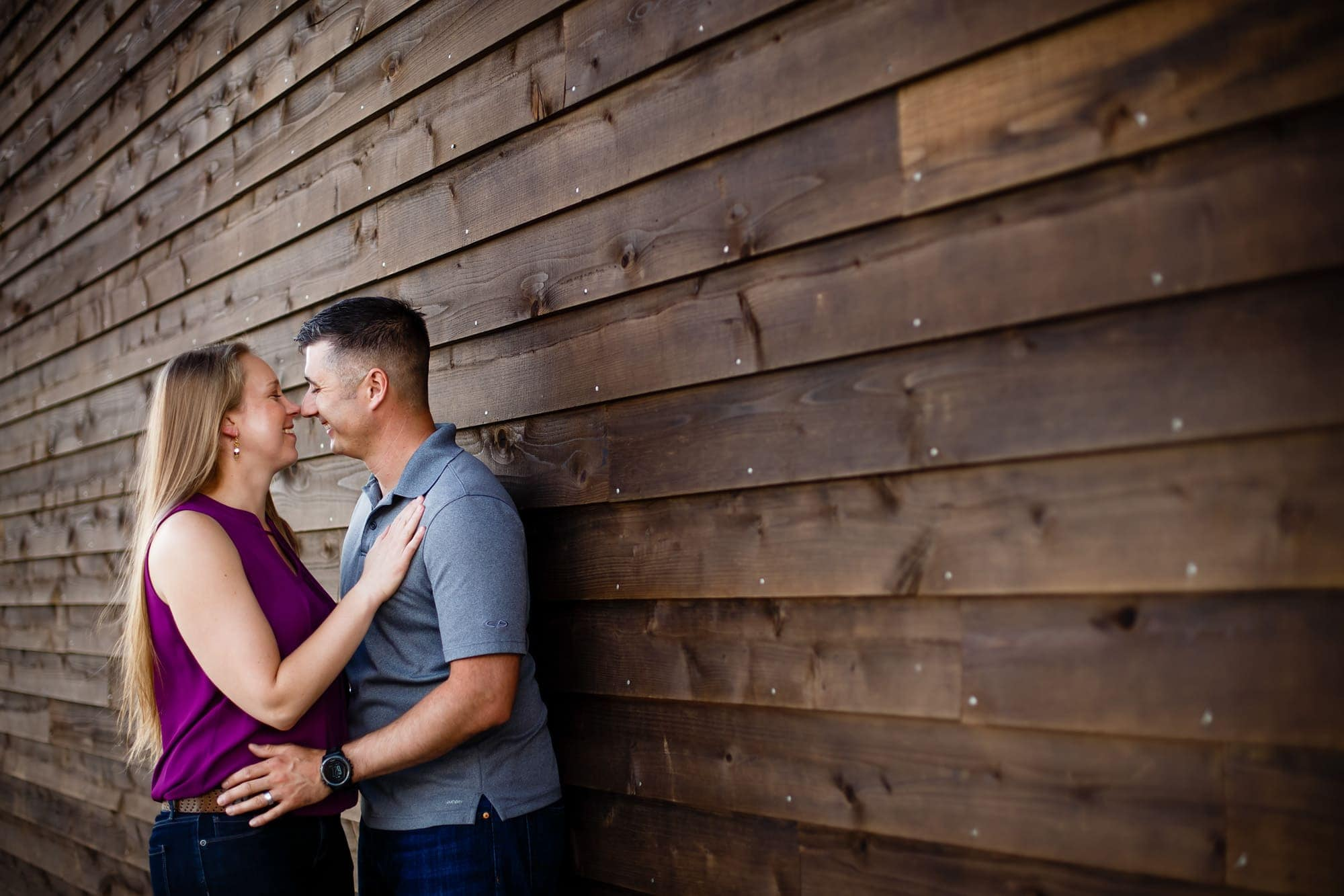 A couple look at each other next to a barn wall to celebrate their engagement in Littleton, Colorado