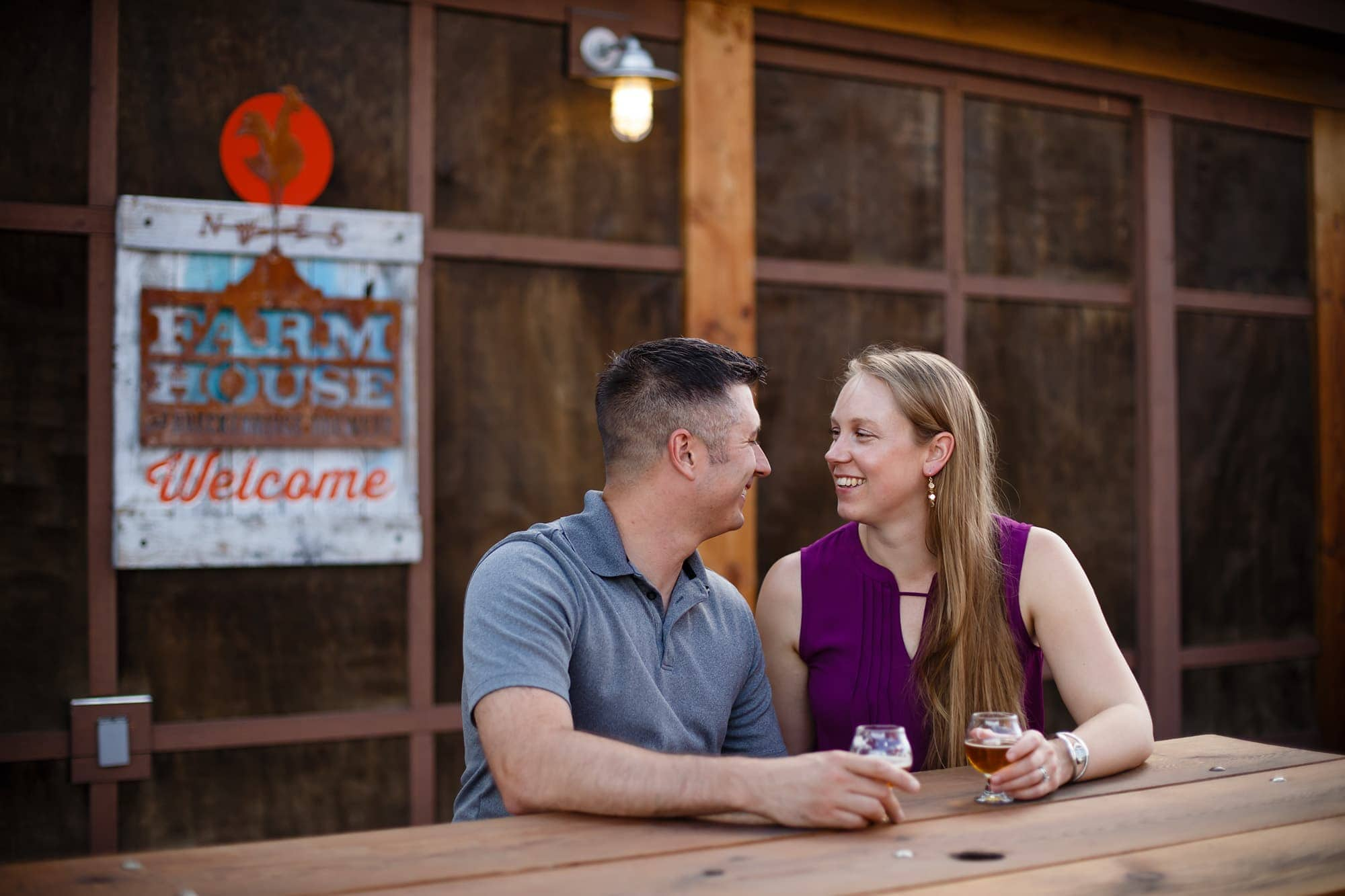 A couple share a beers together as they celebrate their engagement at the Breckenridge Brewery Farm House in Littleton, Colorado.