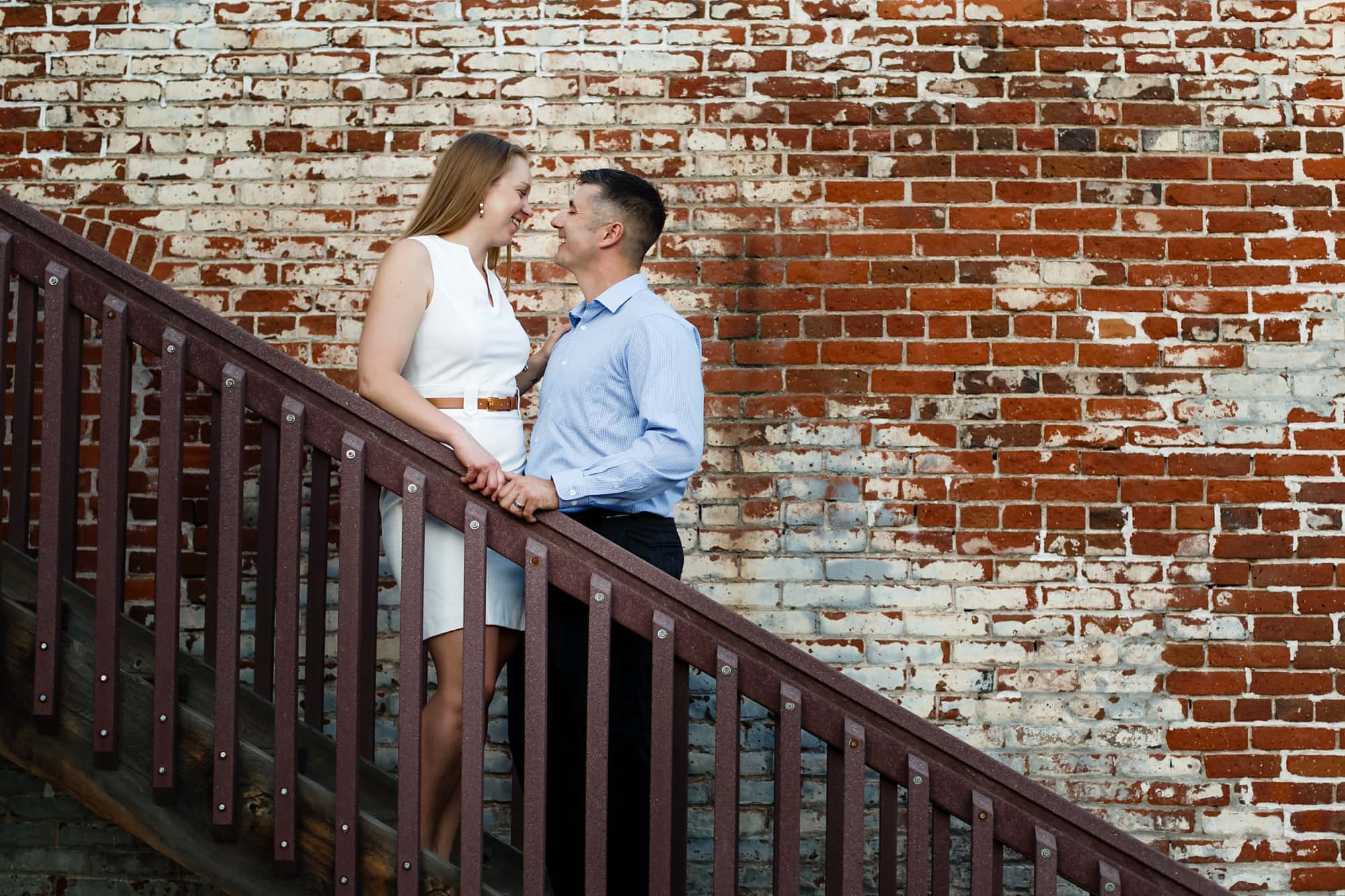 A couple stare into each others eyes in downtown Littleton next to a brick wall.