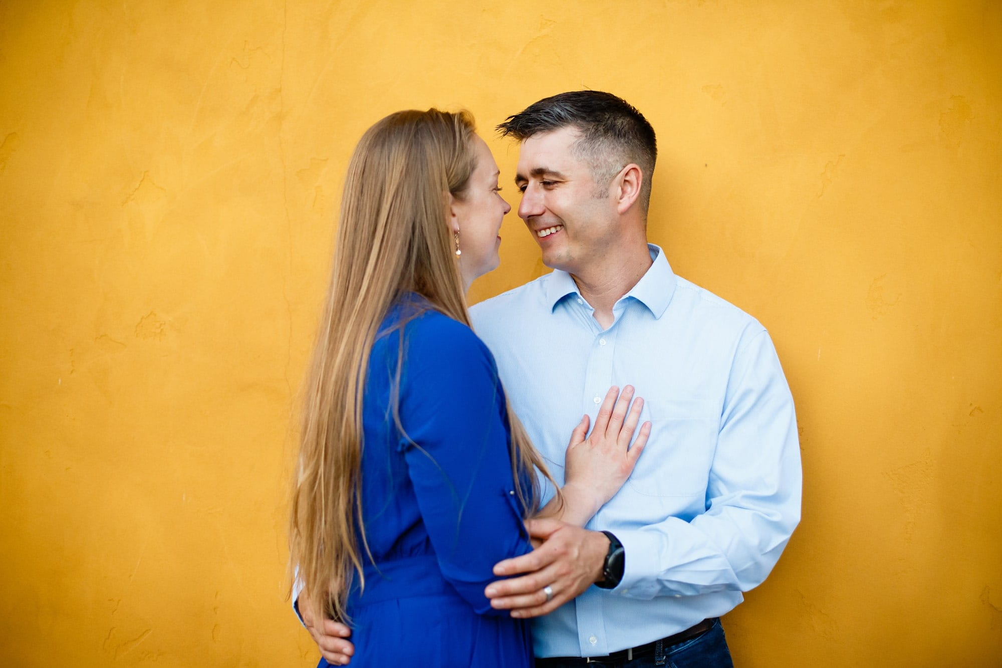 In front of a yellow wall and wearing blue, a couple smile at each other during their engagement portrait session in downtown Littleton Colorado.