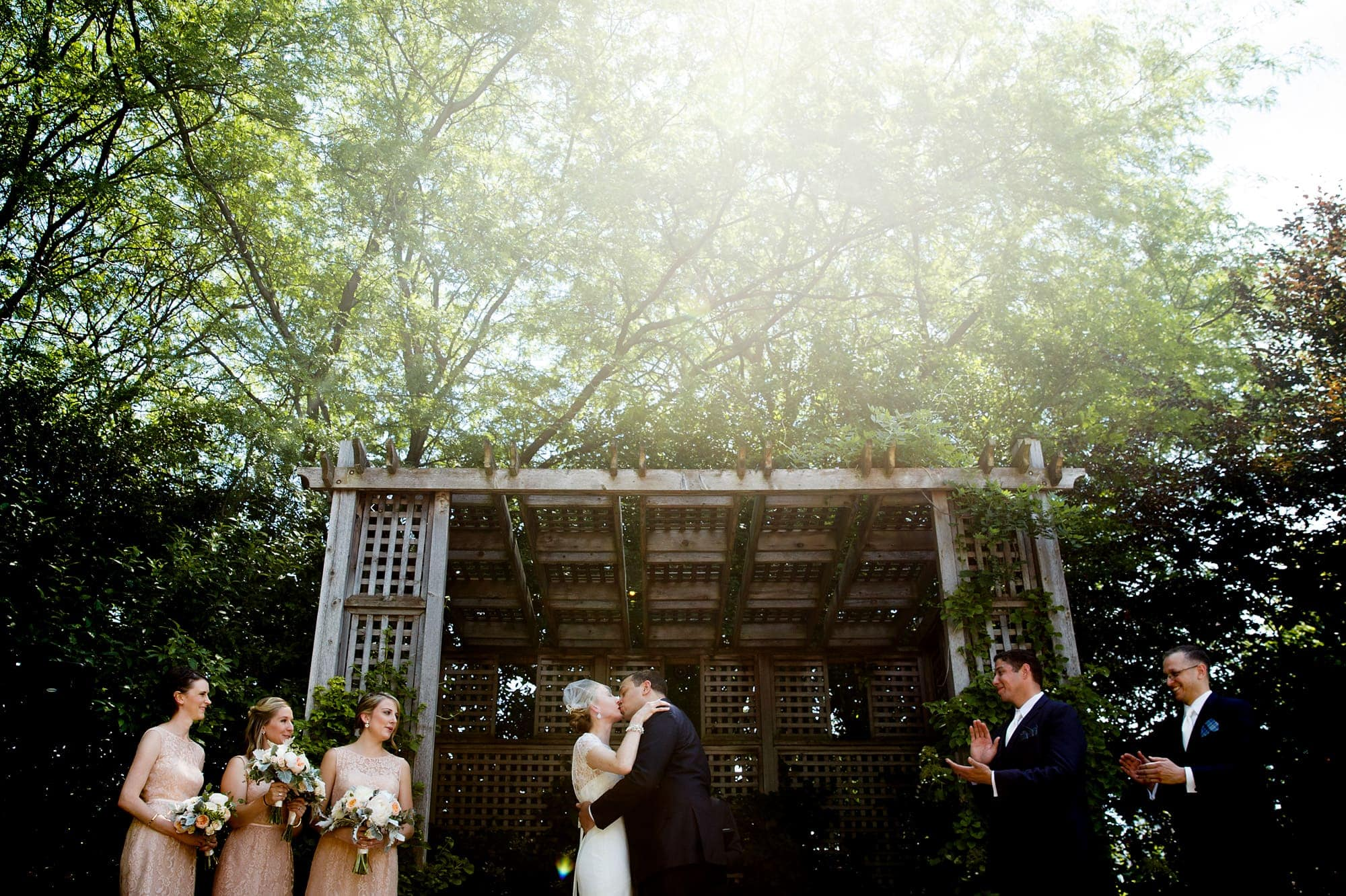 A groom kisses hits bride for the first time under the arbor outside during their morning wedding at Galleria Marchetti in Chicago, Illinois.