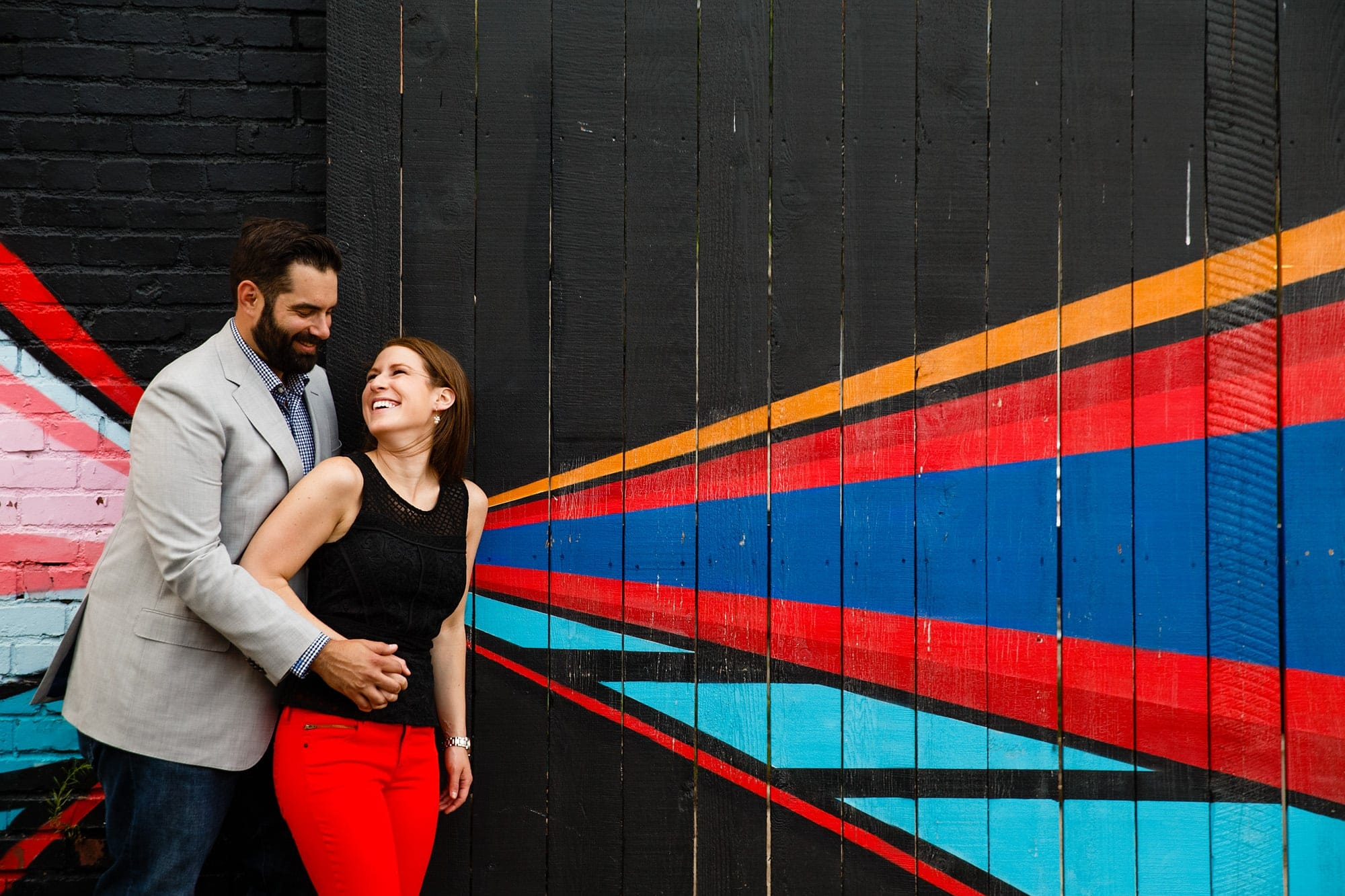 A couple have fun together along a painted grafiti wall on Larimer Street in Denver for their engagment