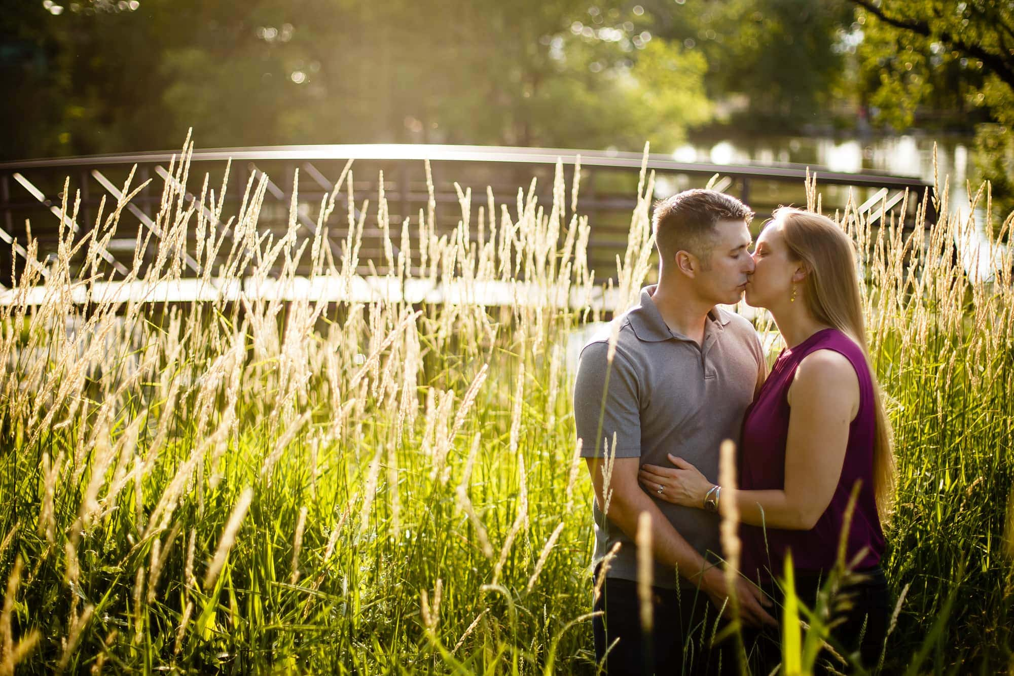 Megan and Bill share a kiss in the long grass along the stream at Sterne Park in Littleton during their engagement session.