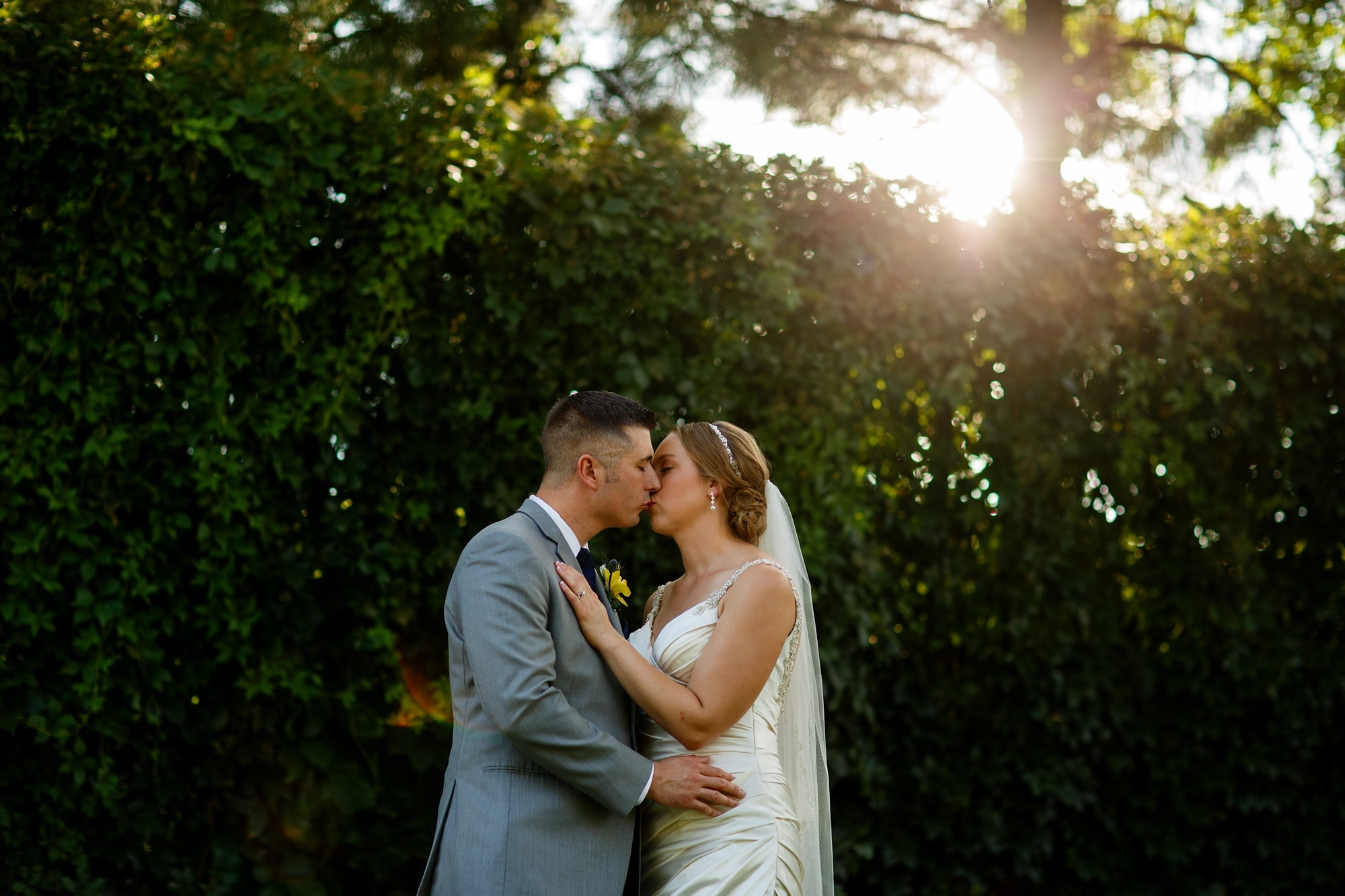 A couple kiss as the sun glows above them near the Denver Zoo beofre their wedding