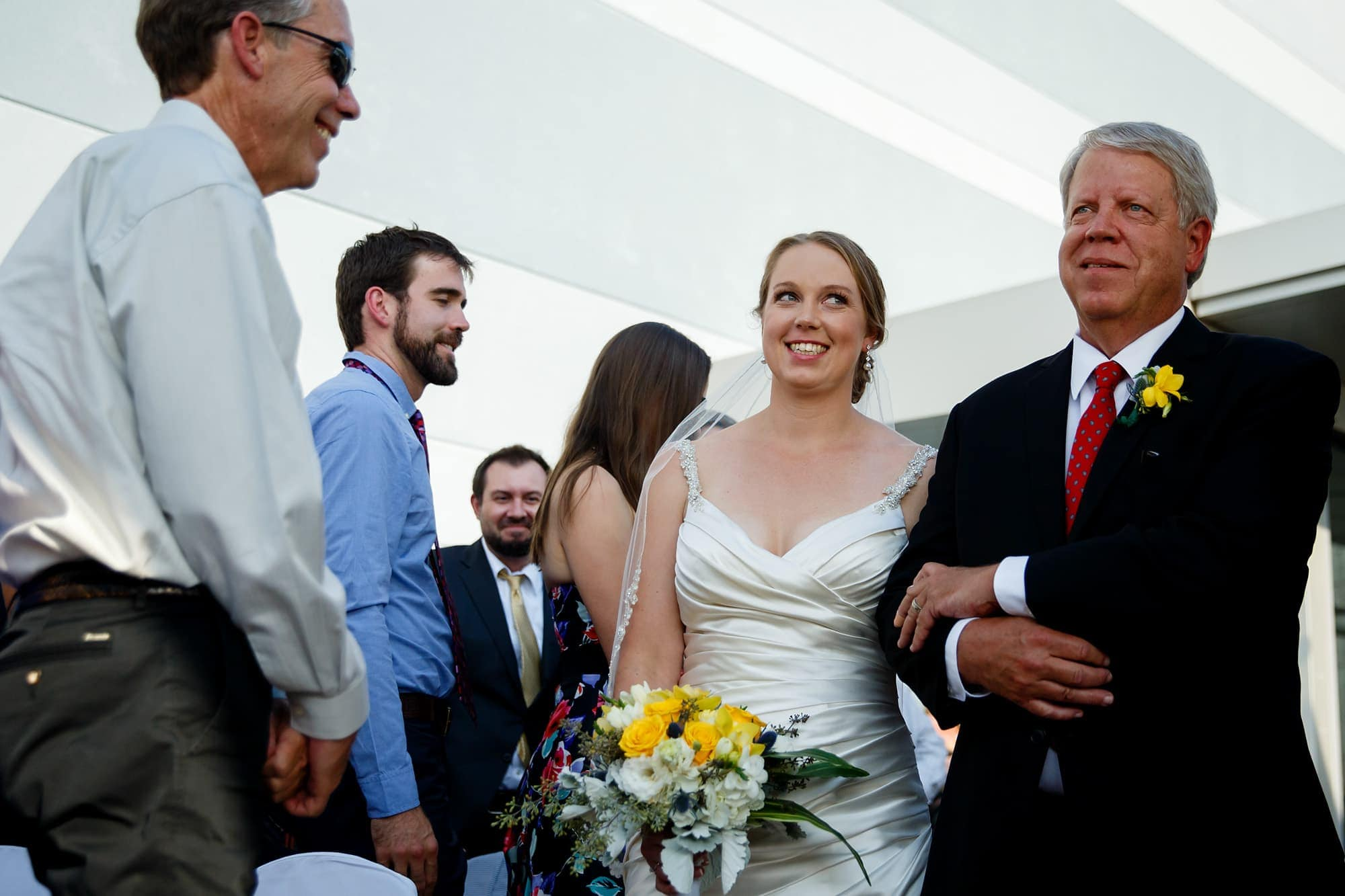 A bride walks down the aisle at the Denver Museum of Nature and Science