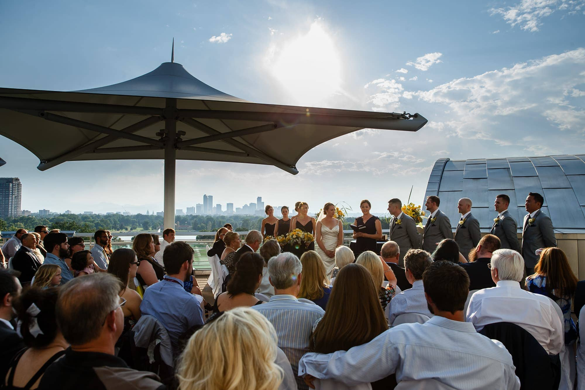 A wedding ceremony takes place on the rooftop deck of the Denver Museum of Nature and Science building as the Denver skyline and mountains can be seen to the west