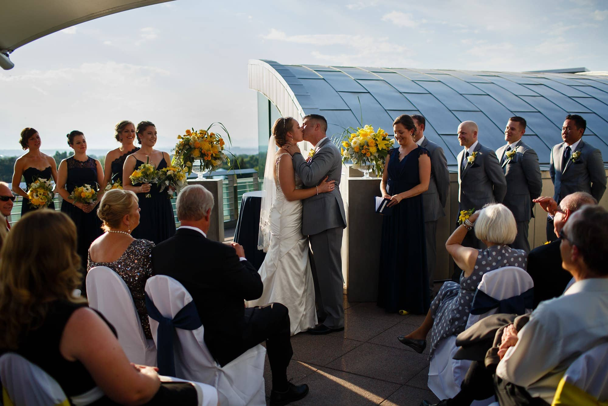 A couple share their first kiss together on the rooftop deck in front of friends and family at the Denver Museum of Nature and Science