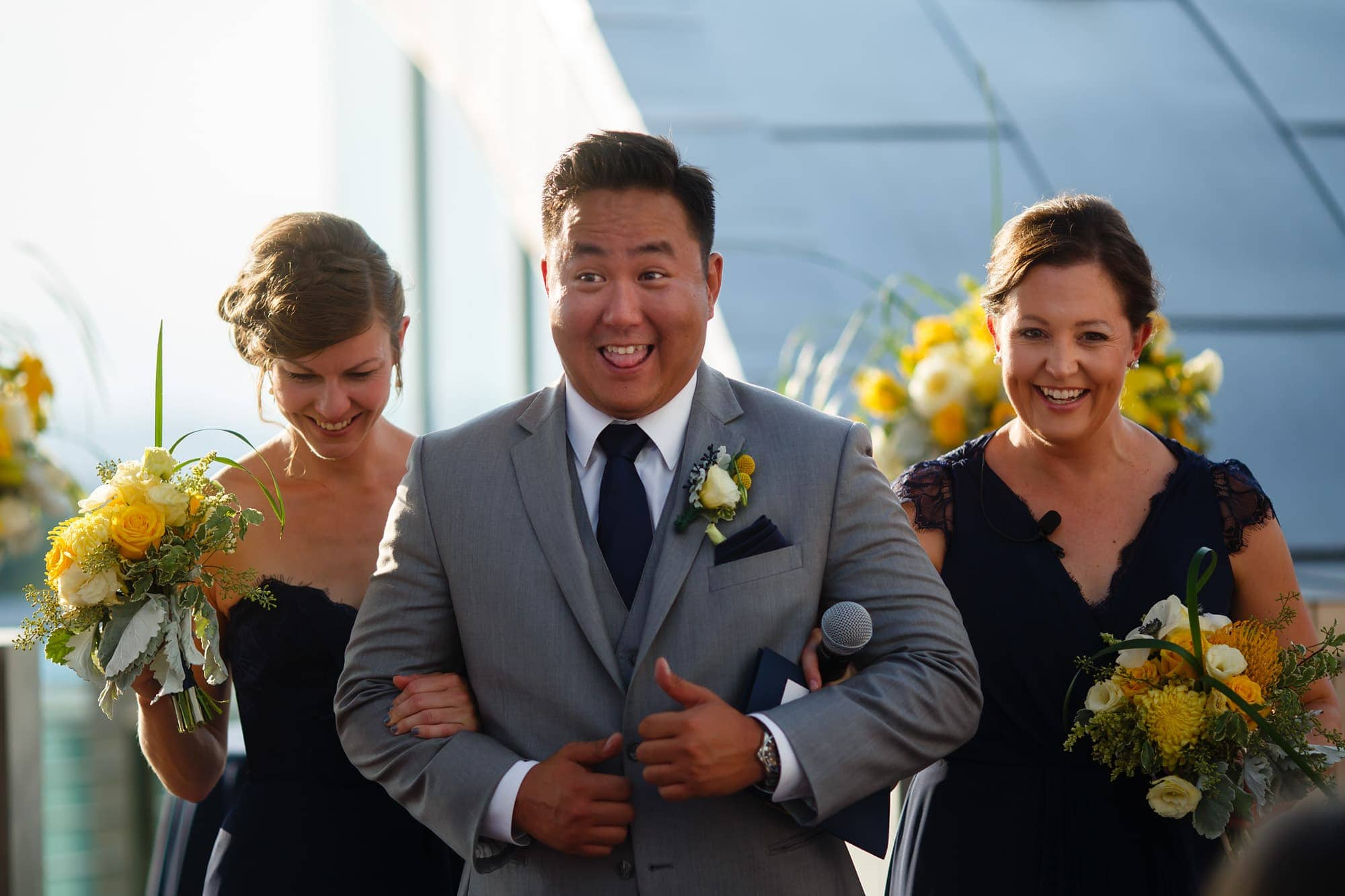 A groomsman gets excited to walk the bridesmaids down the aisle