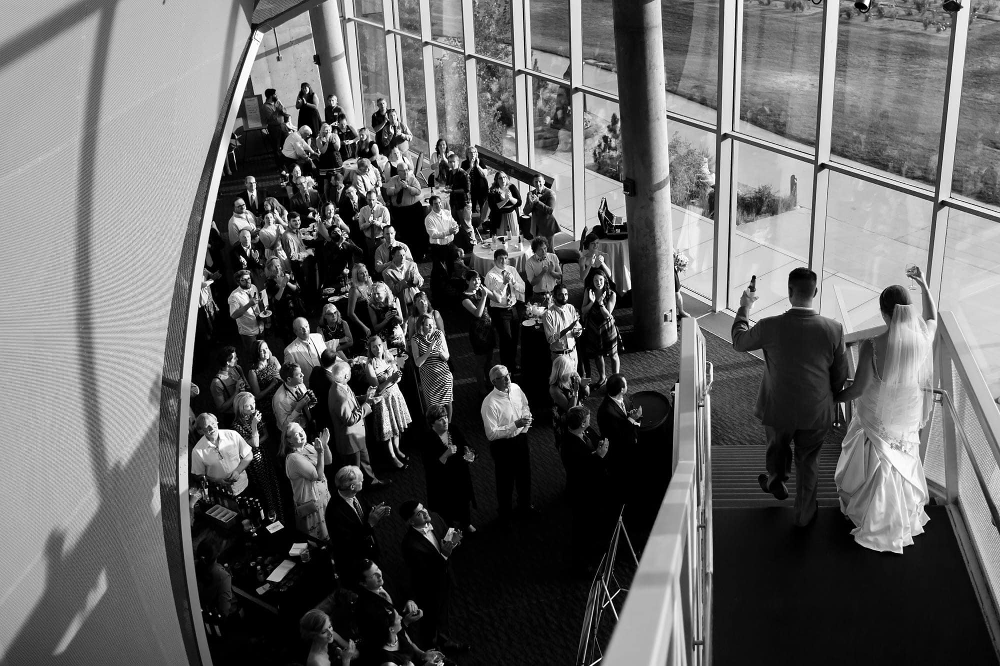 A couple descend the staircase in the west atrium as they are introduced at their reception at the Denver Museum of Nature and Science