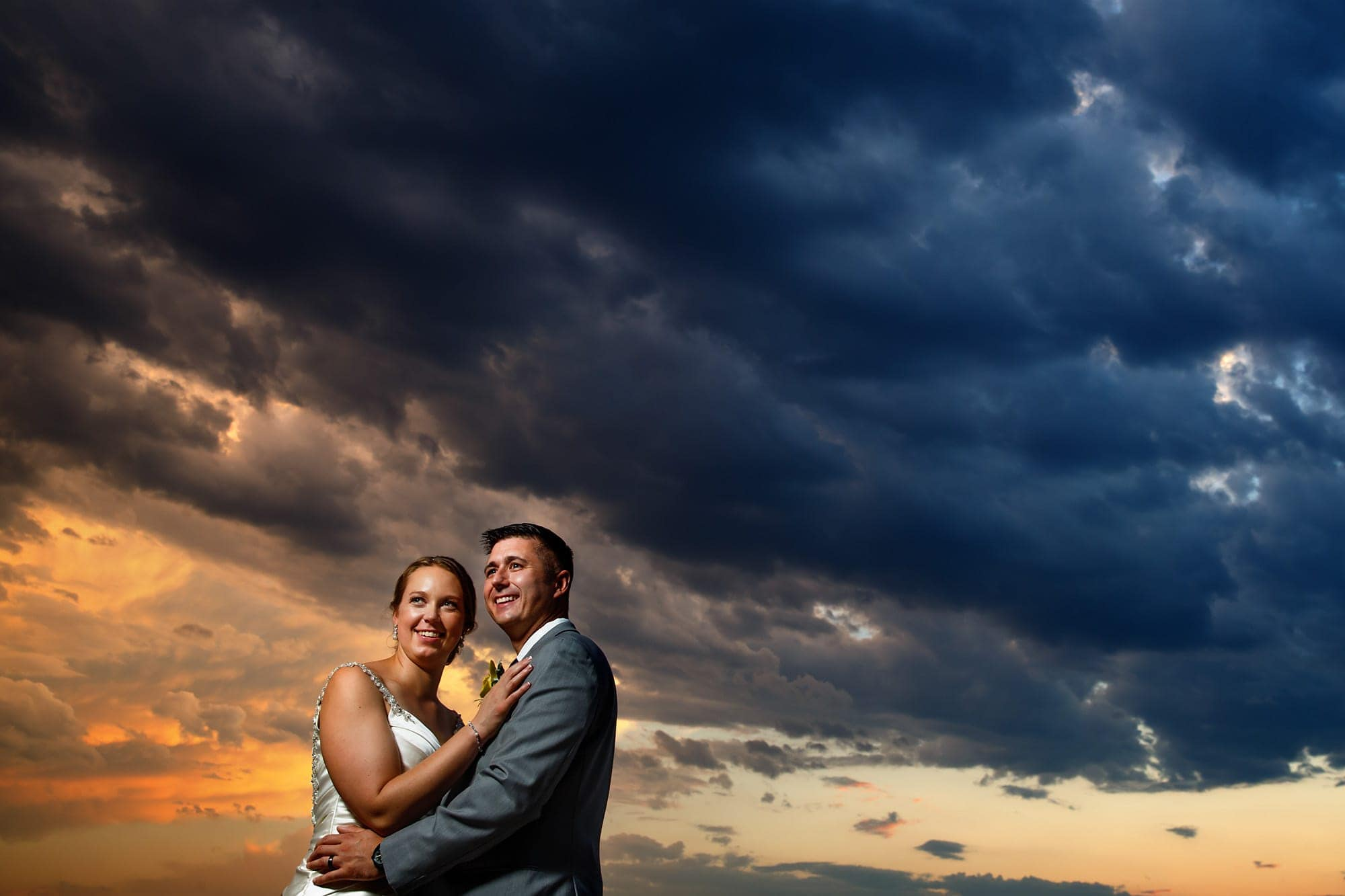 The couple pose during for a portrait as the sun sets behind them after their wedding ceremony at the Denver Museum of Nature and Science