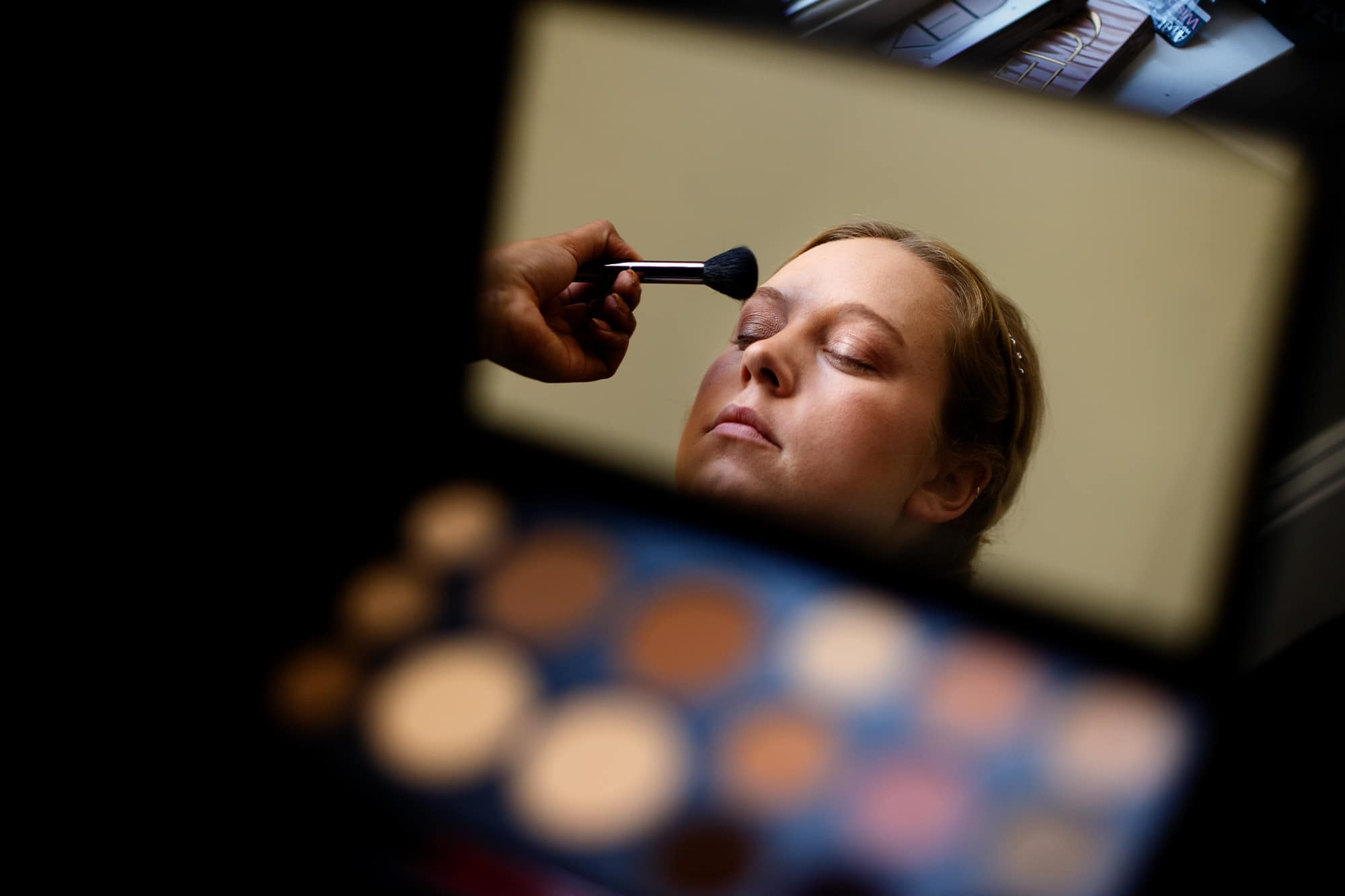 Bride reflected in a compact mirror while getting ready