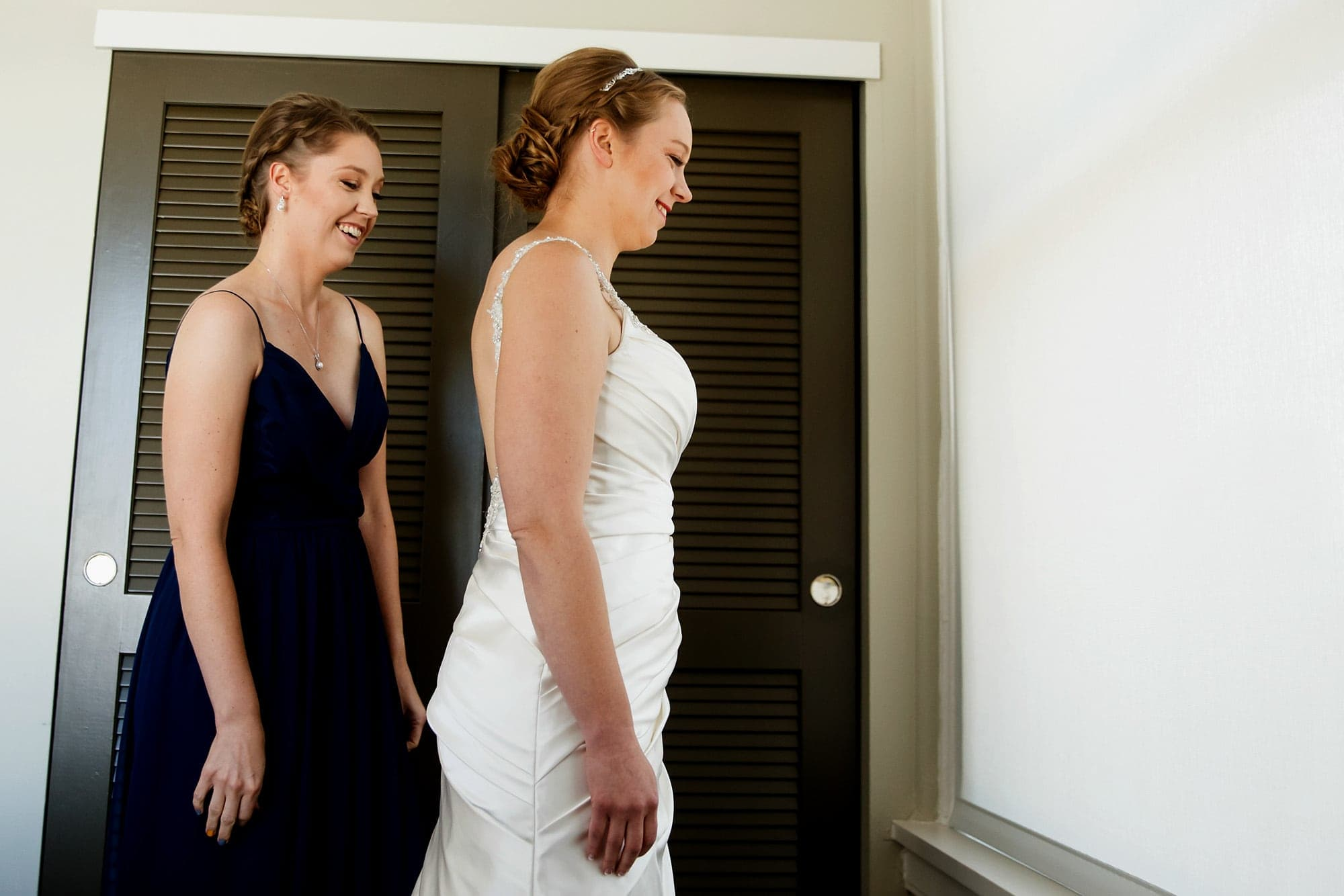 A sister and her bride get into her wedding gown while getting ready at Magnola Hotel