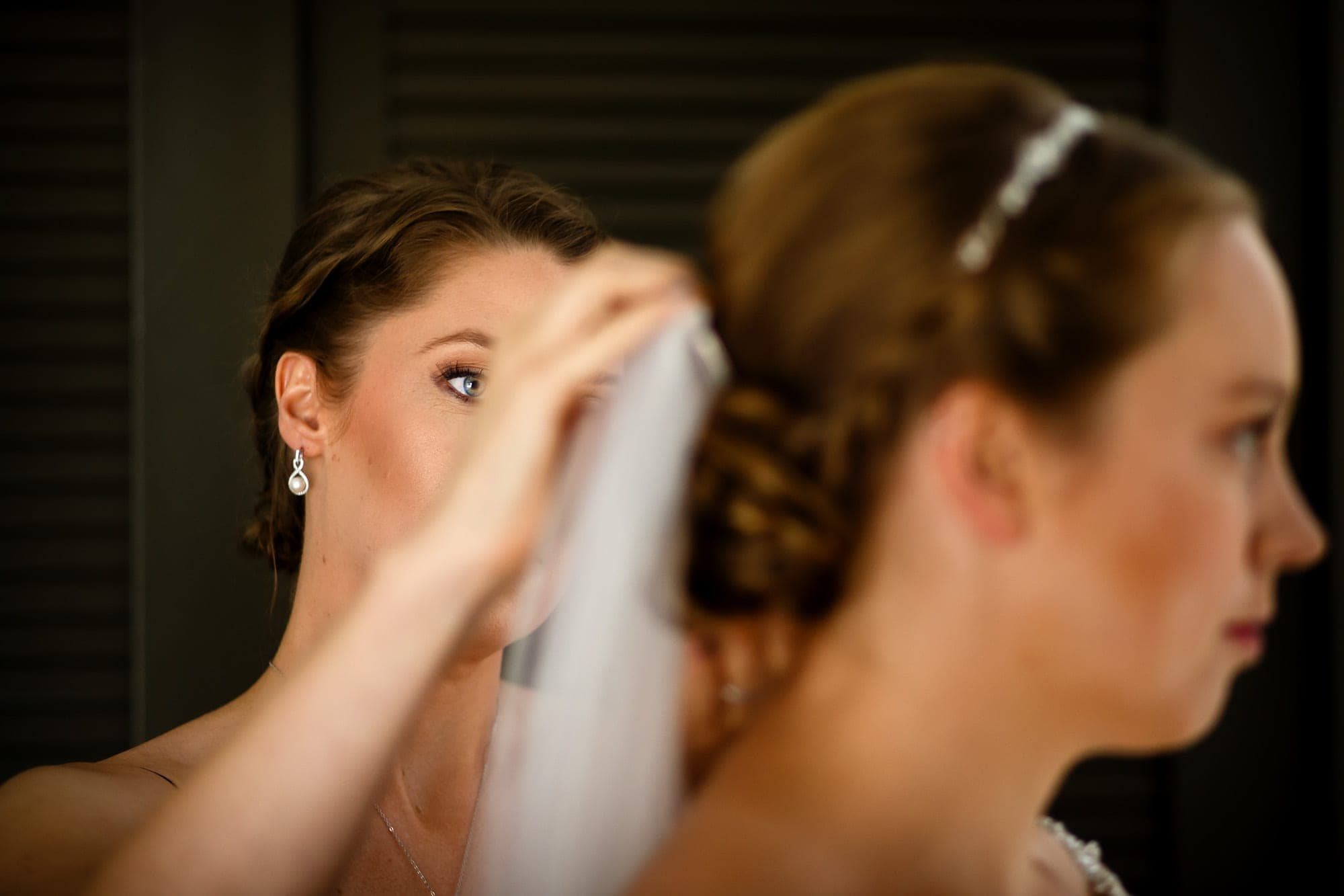 A sister of the bride adjusts the veil before the wedding