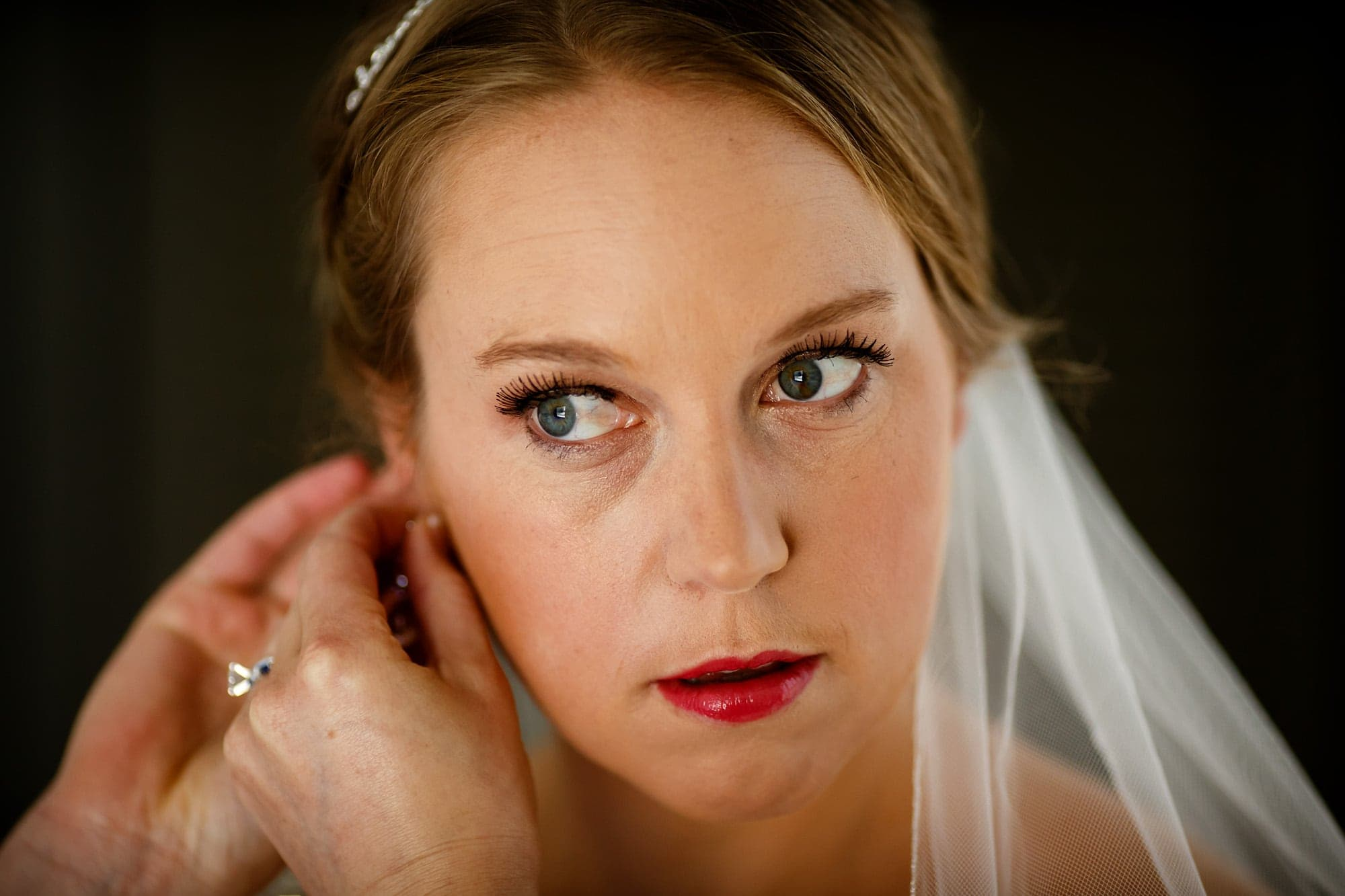 A bride puts her earrings on while looking in the mirror