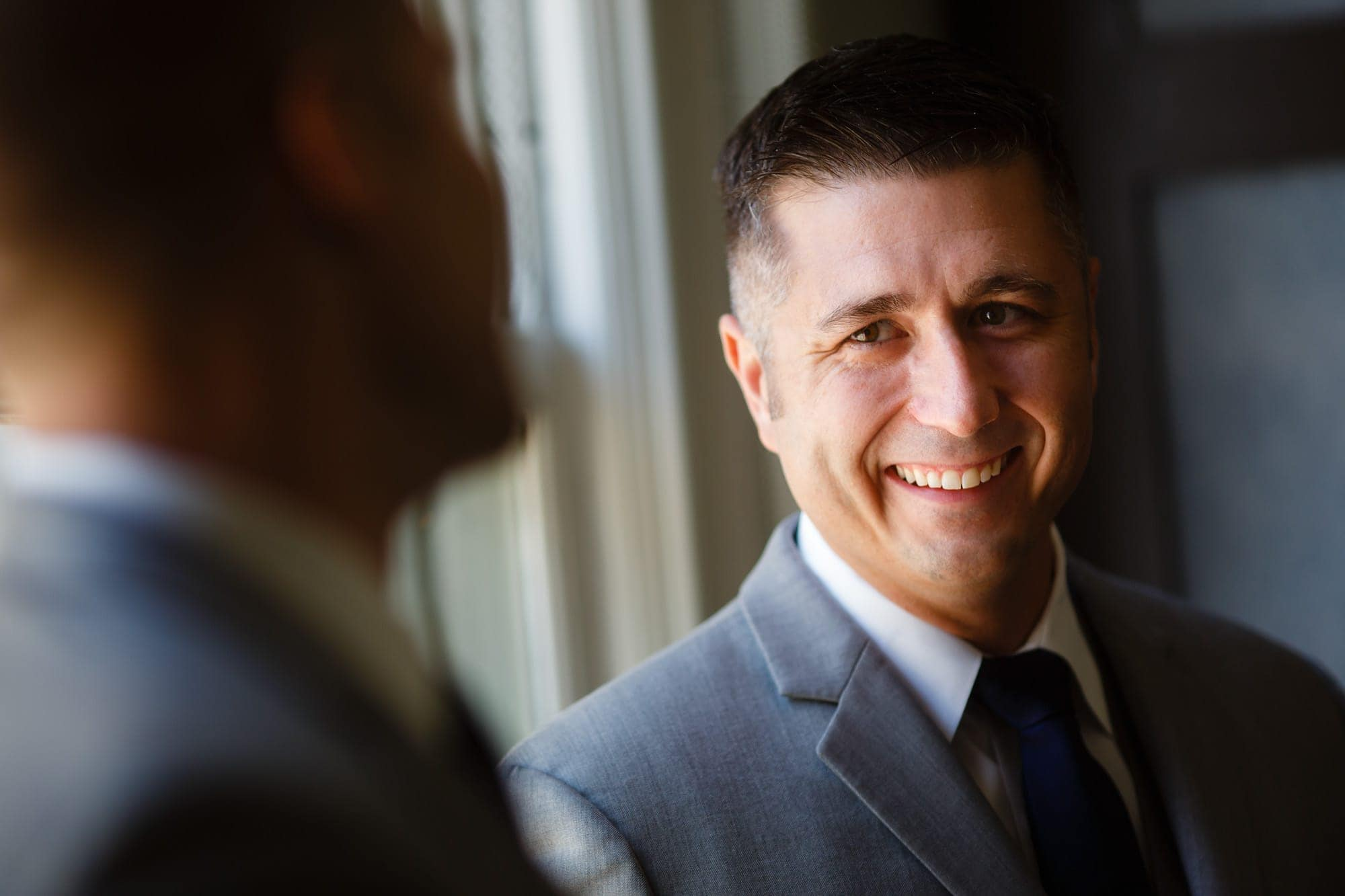 A groom shares a laugh with his groomsmen in Denver at Magnolia Hotel