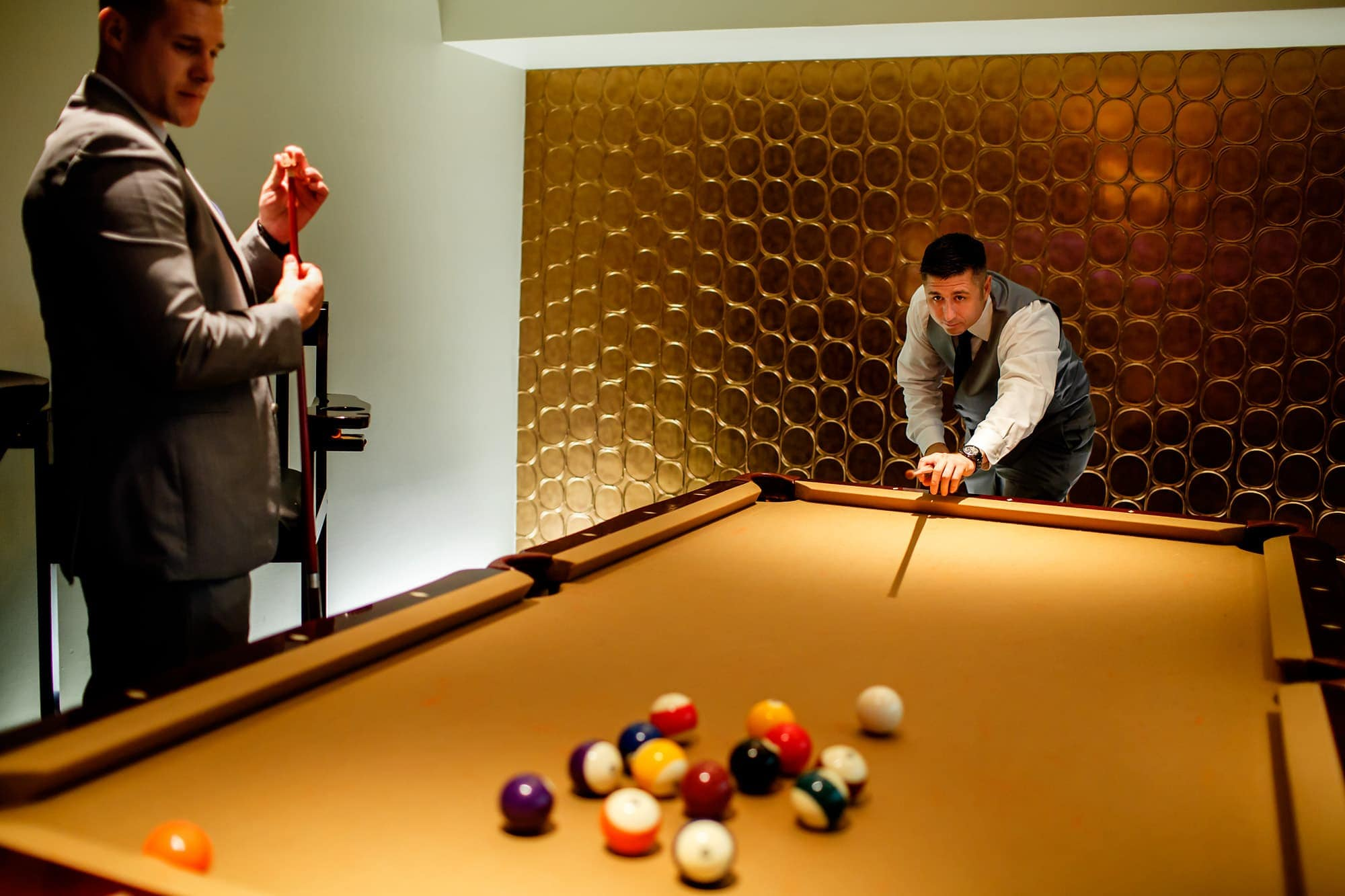 A groom and his groomsmen play pool and billards at Magnolia Hotel in Denver before the wedding