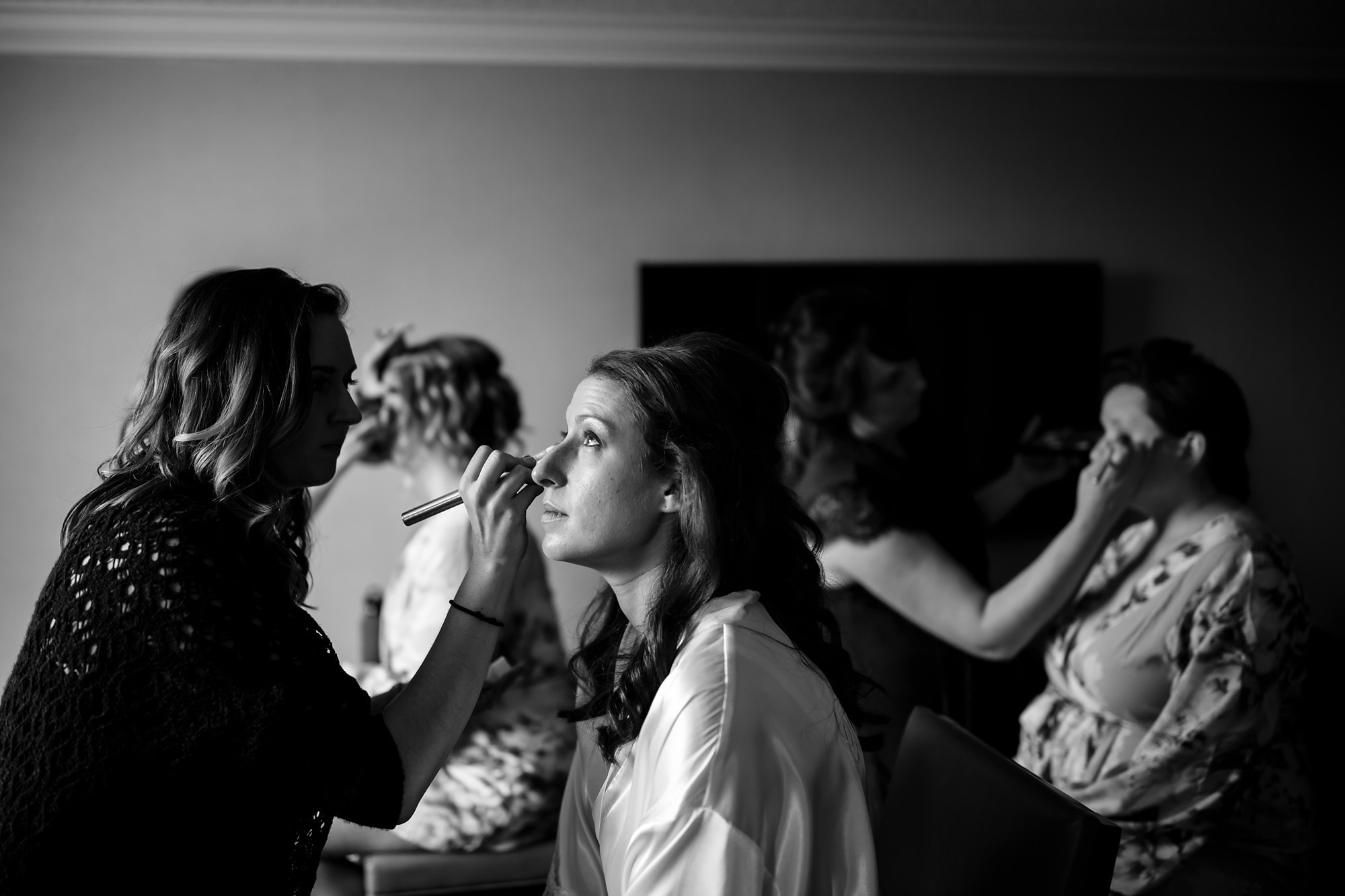 The bride gets her makeup done with bridesmaids