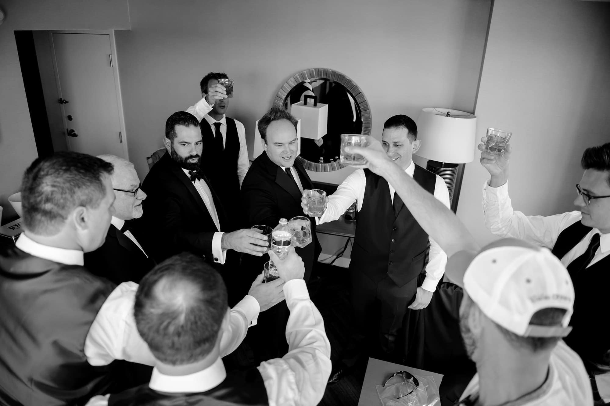 Groomsmen toast rye whiskey while getting ready at the Colorado Springs Marriott